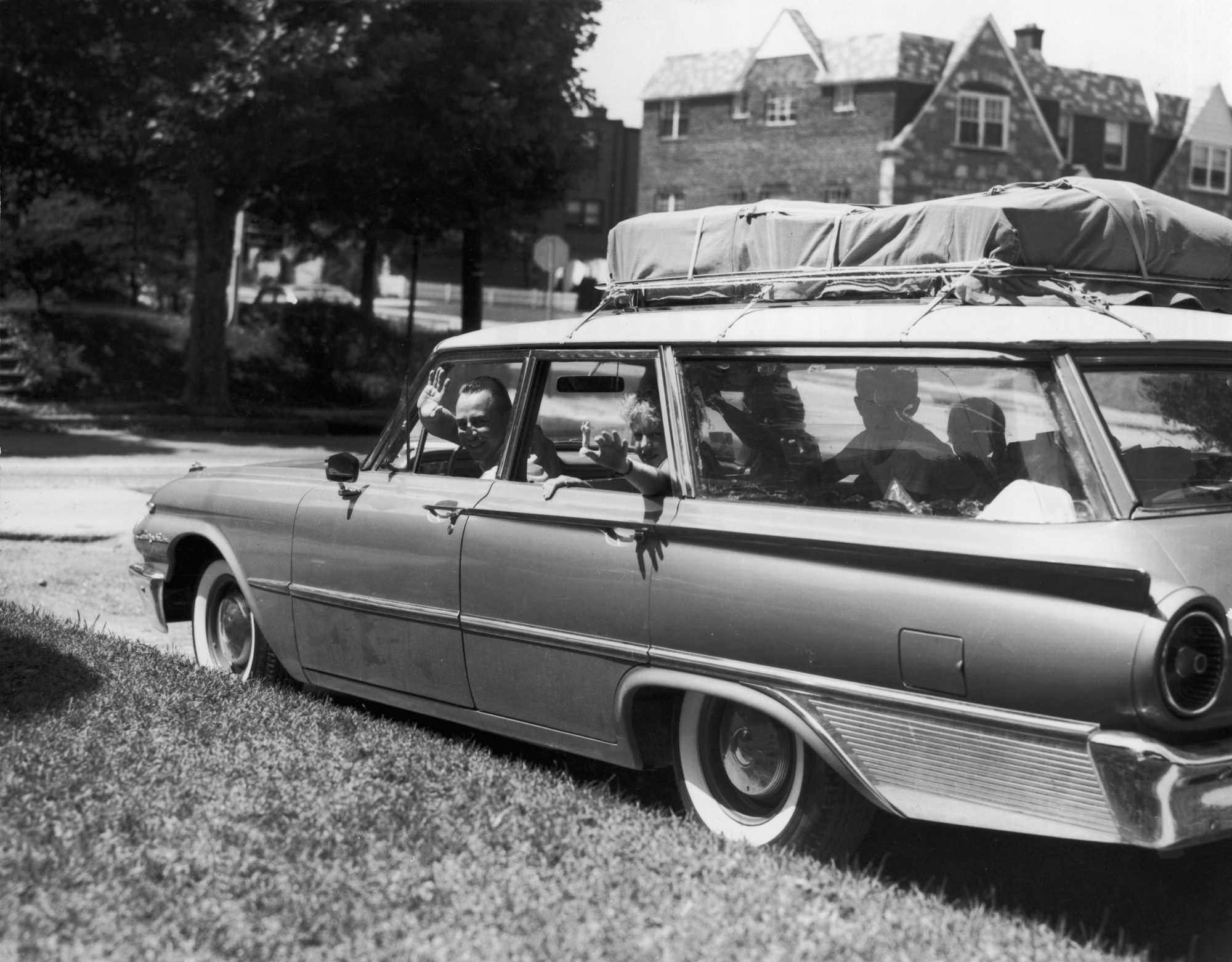 Family Waiving Out Packed Car