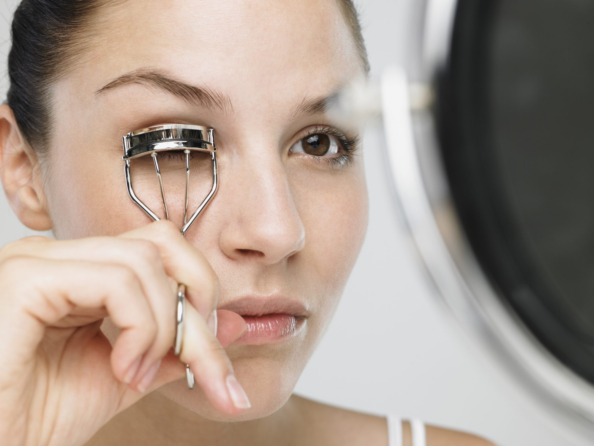 Woman Using Eyelash Curler