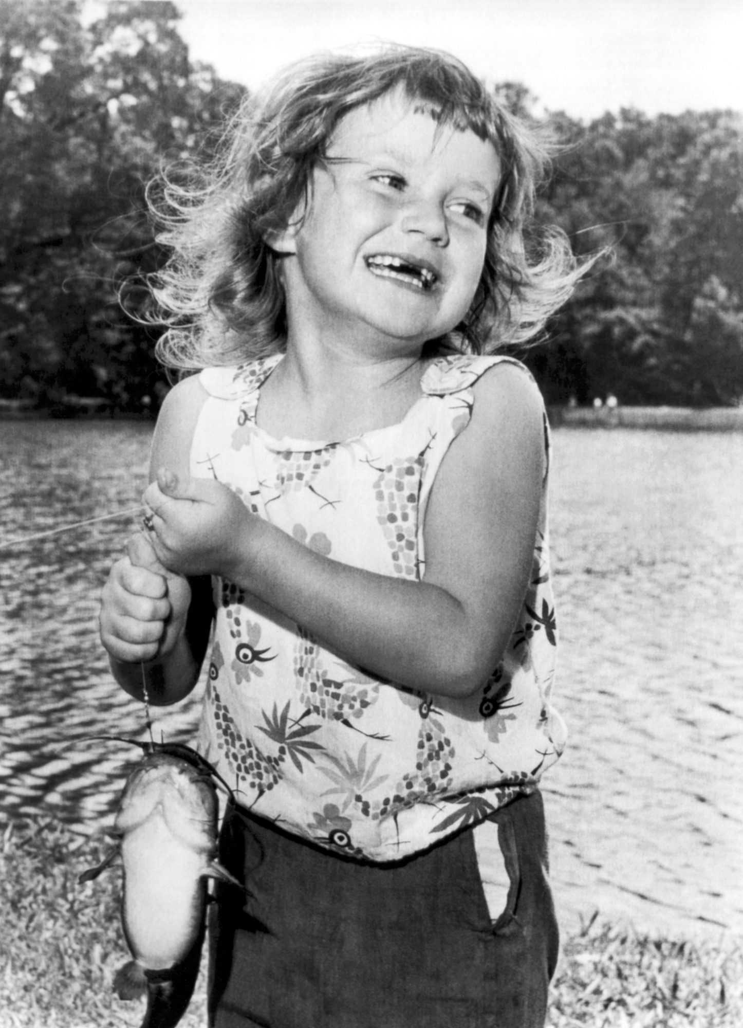 happy little girl holding fish