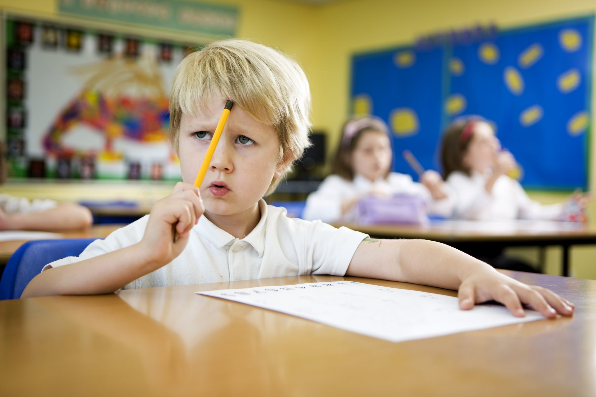 Little Boy Sitting at School Desk with Pencil