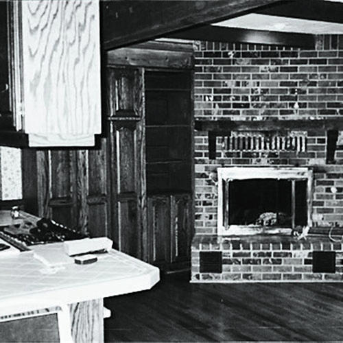 a before photo of a kitchen space with an island cabinet to the left, brown built-in shelving in the middle and an older fireplace off of the main section of the kitchen