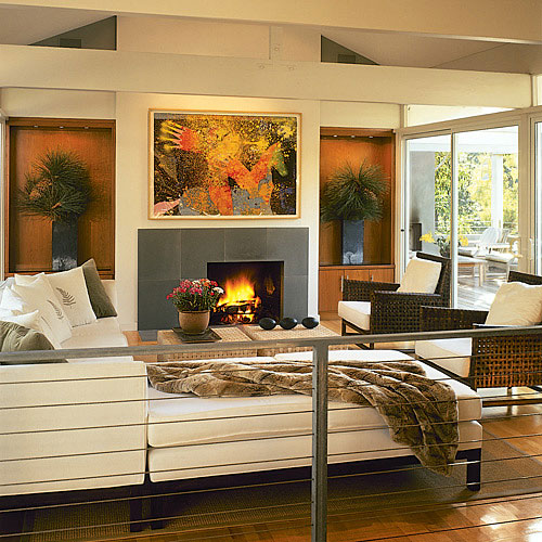 Modern, sleek living room with a wraparound white couch which faces a fireplace. the living room also has a metal gray railing surround and define the space.
