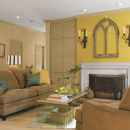yellow walls highlight the artwork above the family room fireplace while the couch faces a clear, glass, mod coffee table