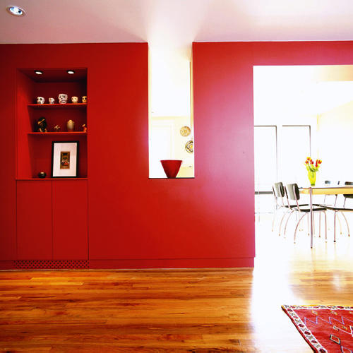 walls in this living room are saturated with deep red hues and inset, built-in shelving accents accessories and a framed painting