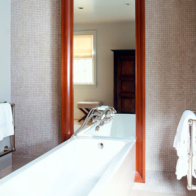 floor to ceiling framed mirror rests on the wall behind a modern, sleek, white bath tub