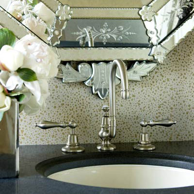 a close up view of a classic bathroom faucet with a decorative patterned mirror behind it and dark countertop