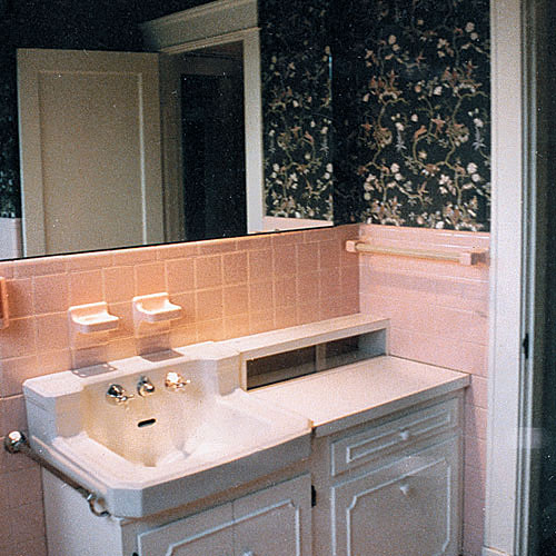 a before photo of a bathroom with pink tile around the sink area and dark, black flowered wallpaper