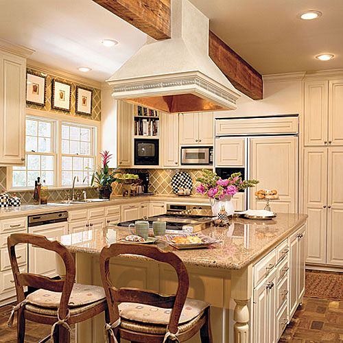 creamy kitchen cabinets that also covered the front of the refrigerator, dish washer, and a granite kitchen island countertop and copper-lined stove hood above the island
