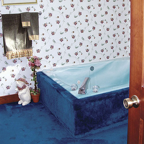 bright blue carpet runs up along the sides of the tub and outdated wallpaper with small flowers off-sets this dated master bathroom