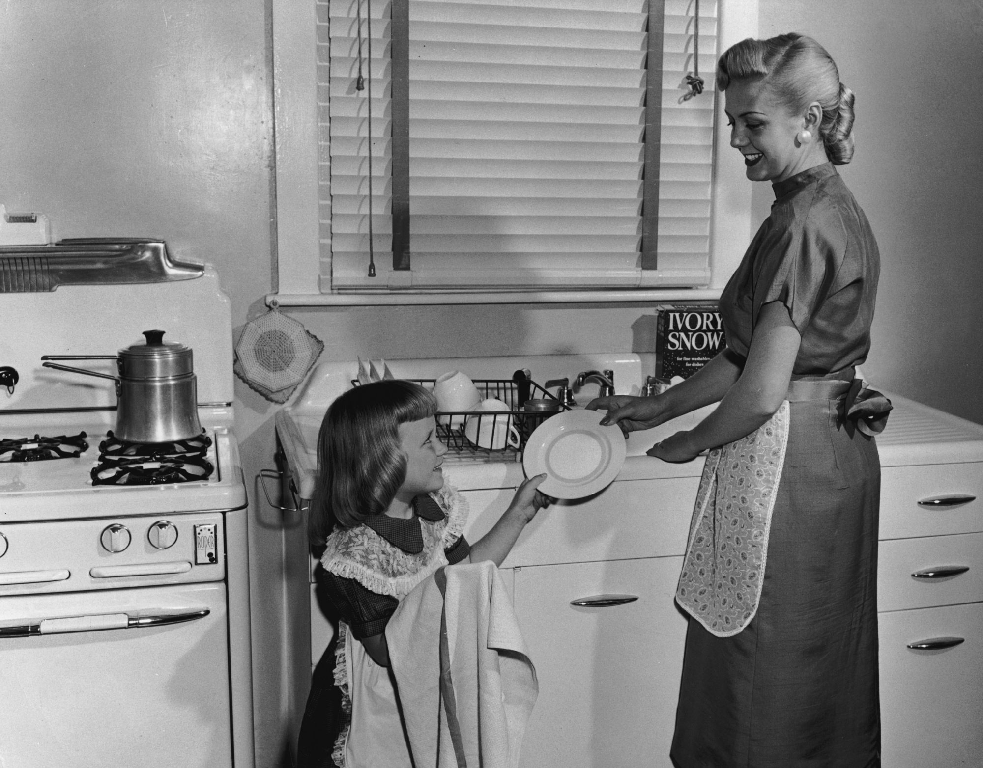 Vintage photo of child helping mother clean dishes