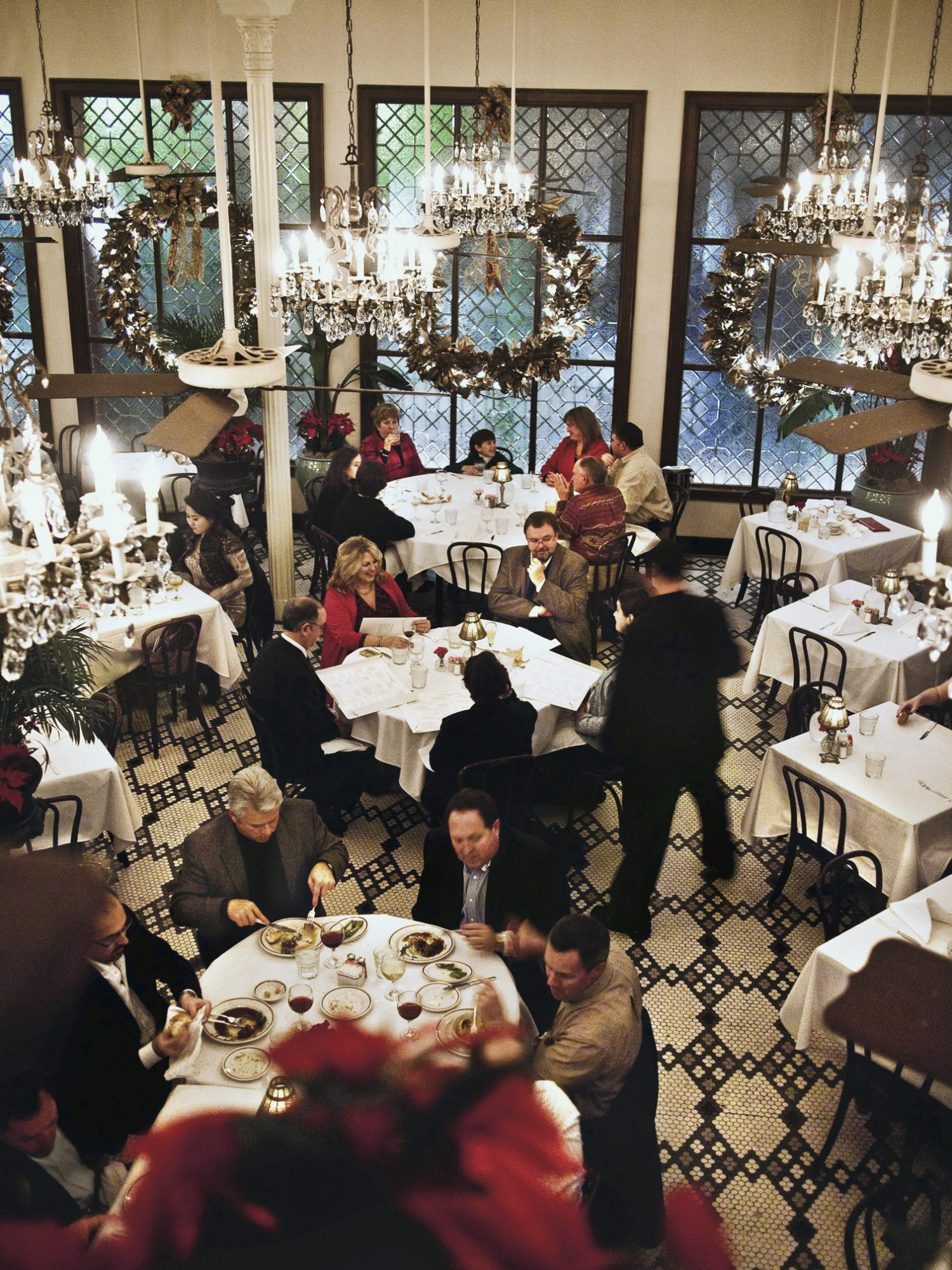 Arnaud's Restaurant showing people sitting at dining tables during Reveillon Dinner.