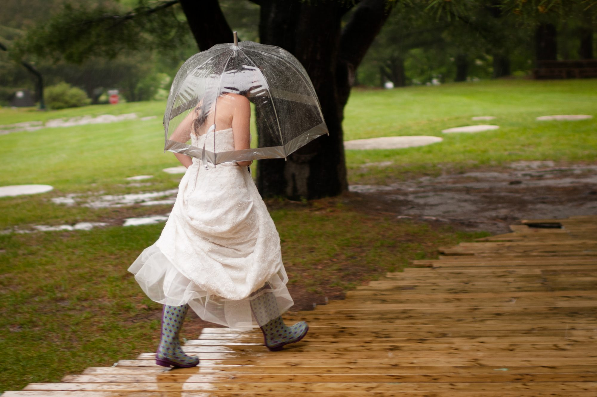 Bride in rain with umbrella and rainboots