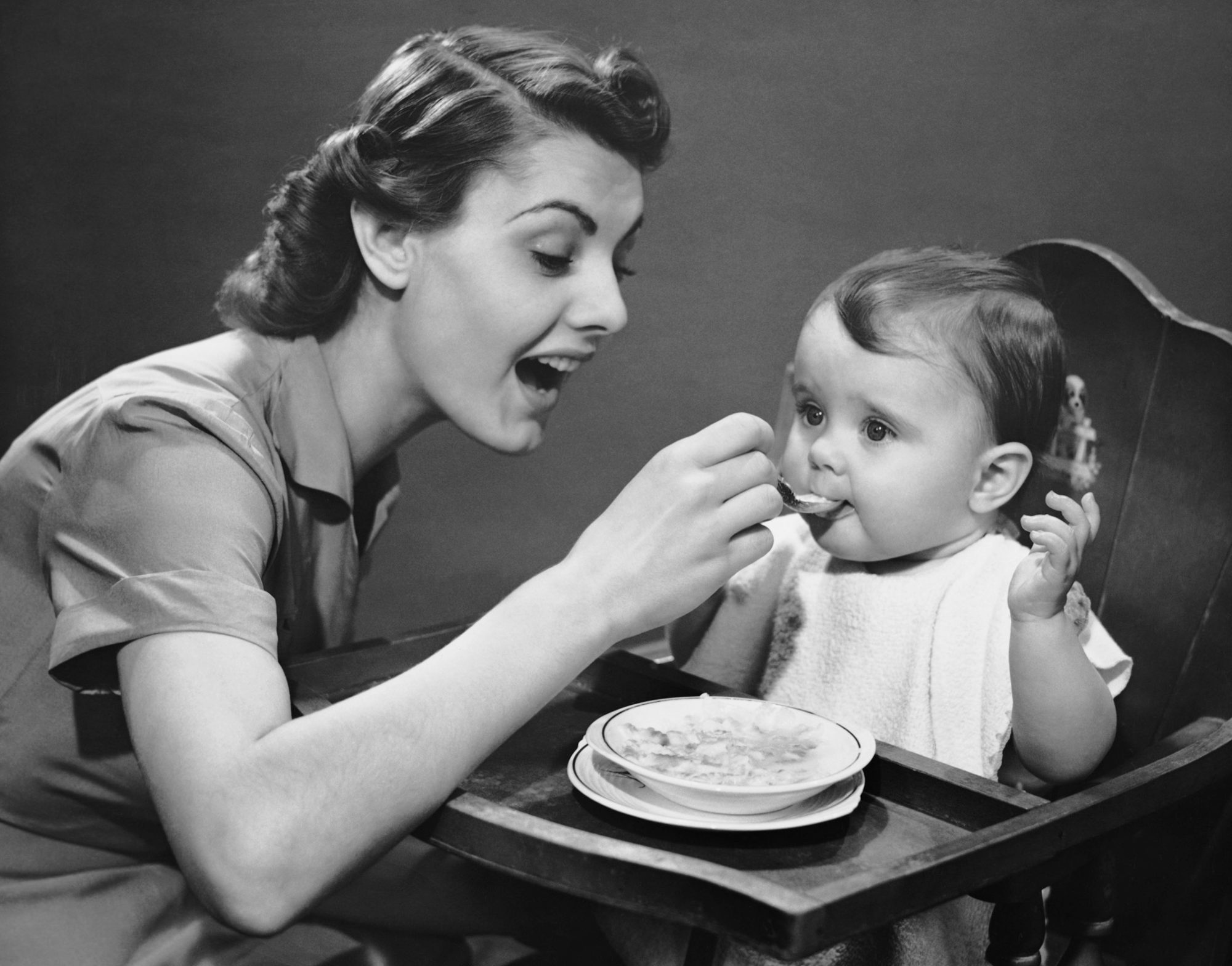 Mother feeding baby vintage photo