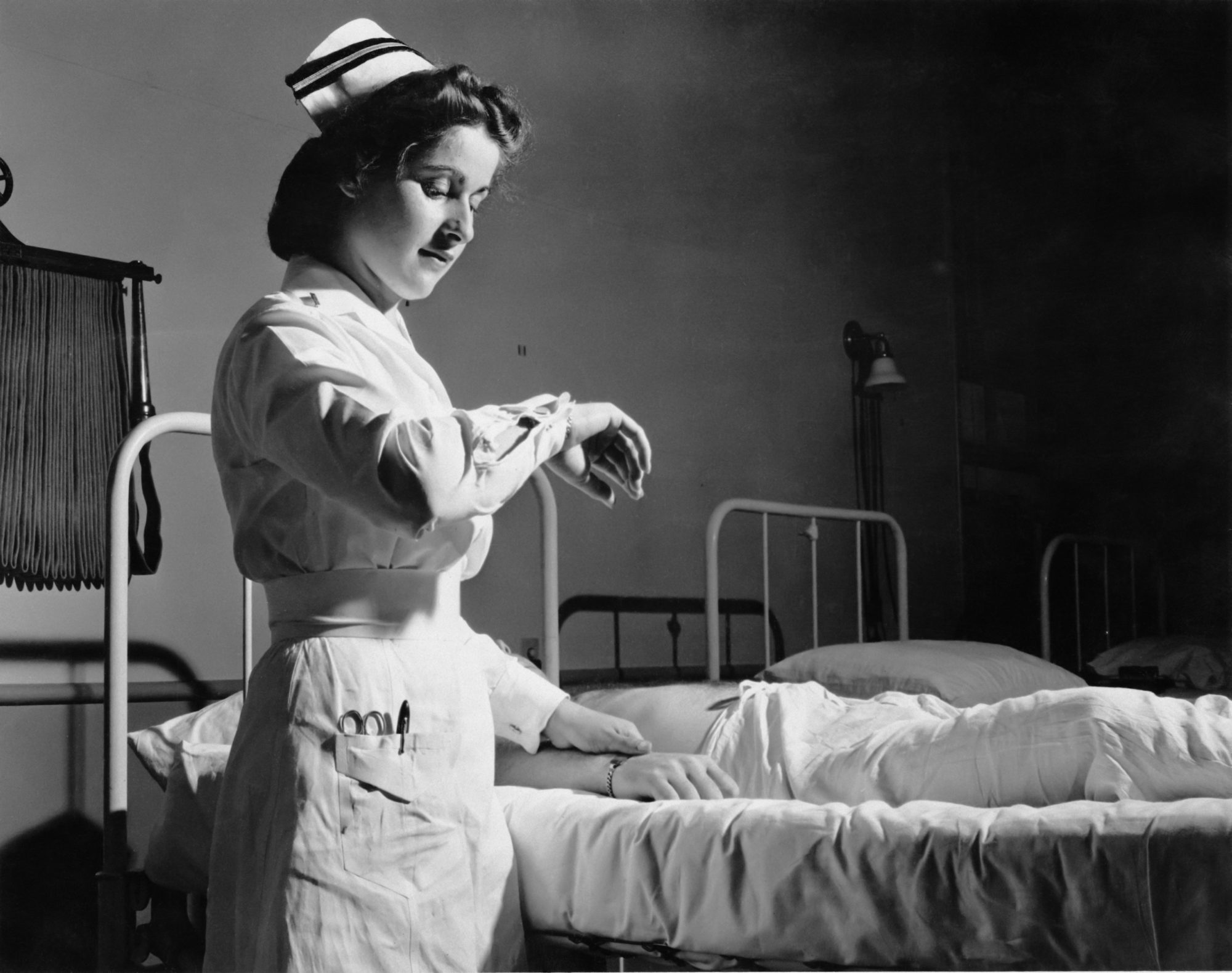 1950s nurse taking pulse of patient