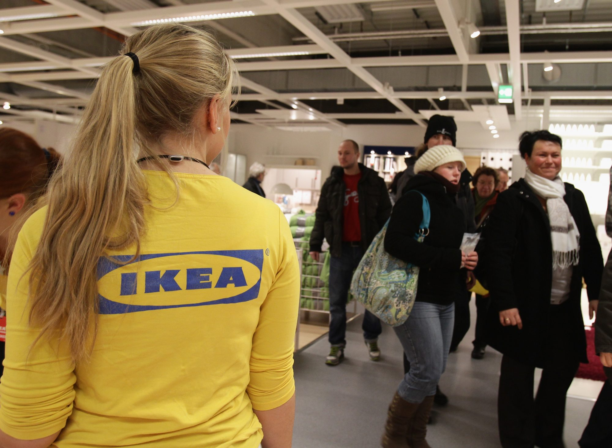 An Ikea employee watches customers shopping during a store opening.