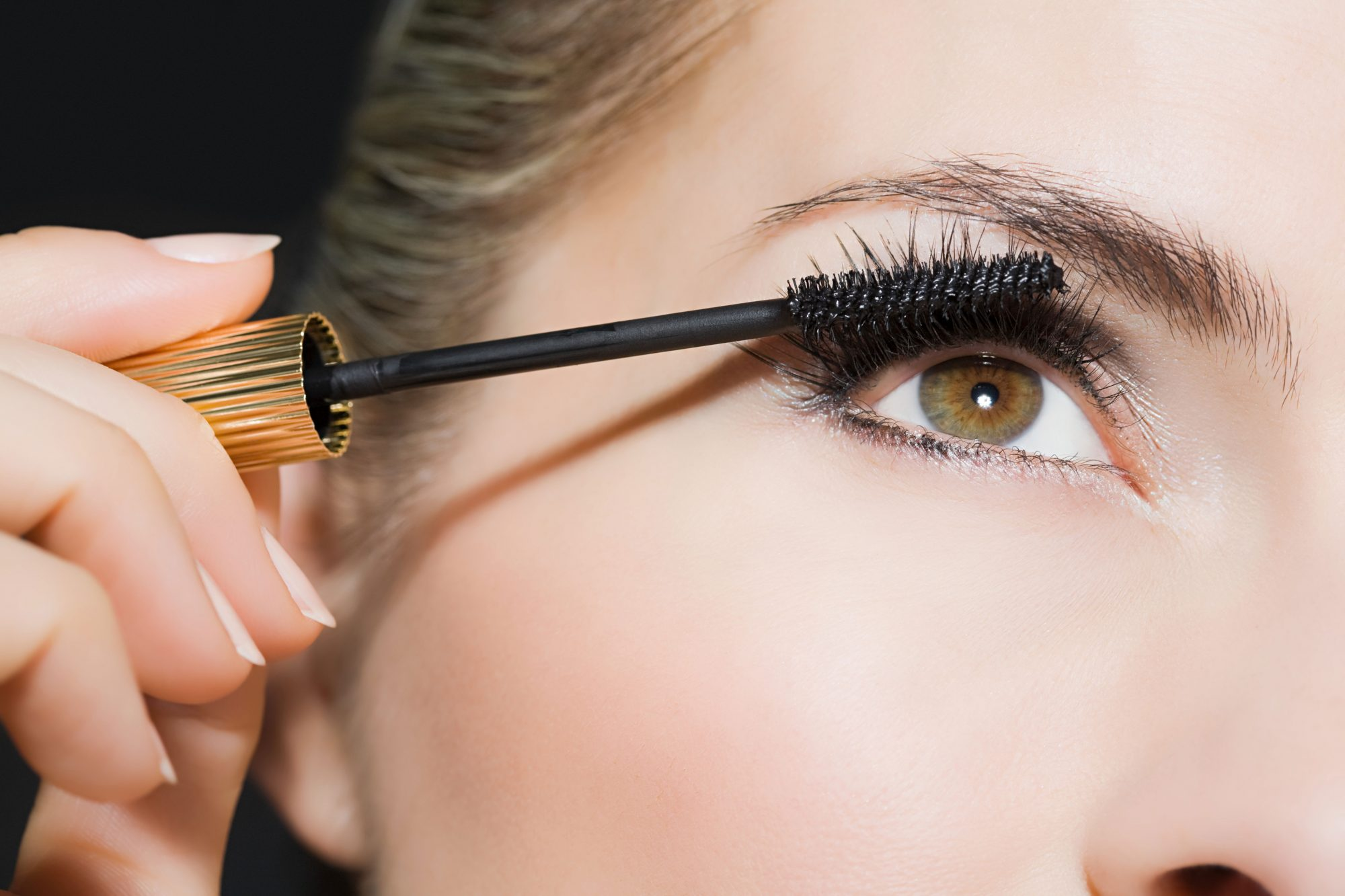 Woman with Green Eyes Applying Mascara
