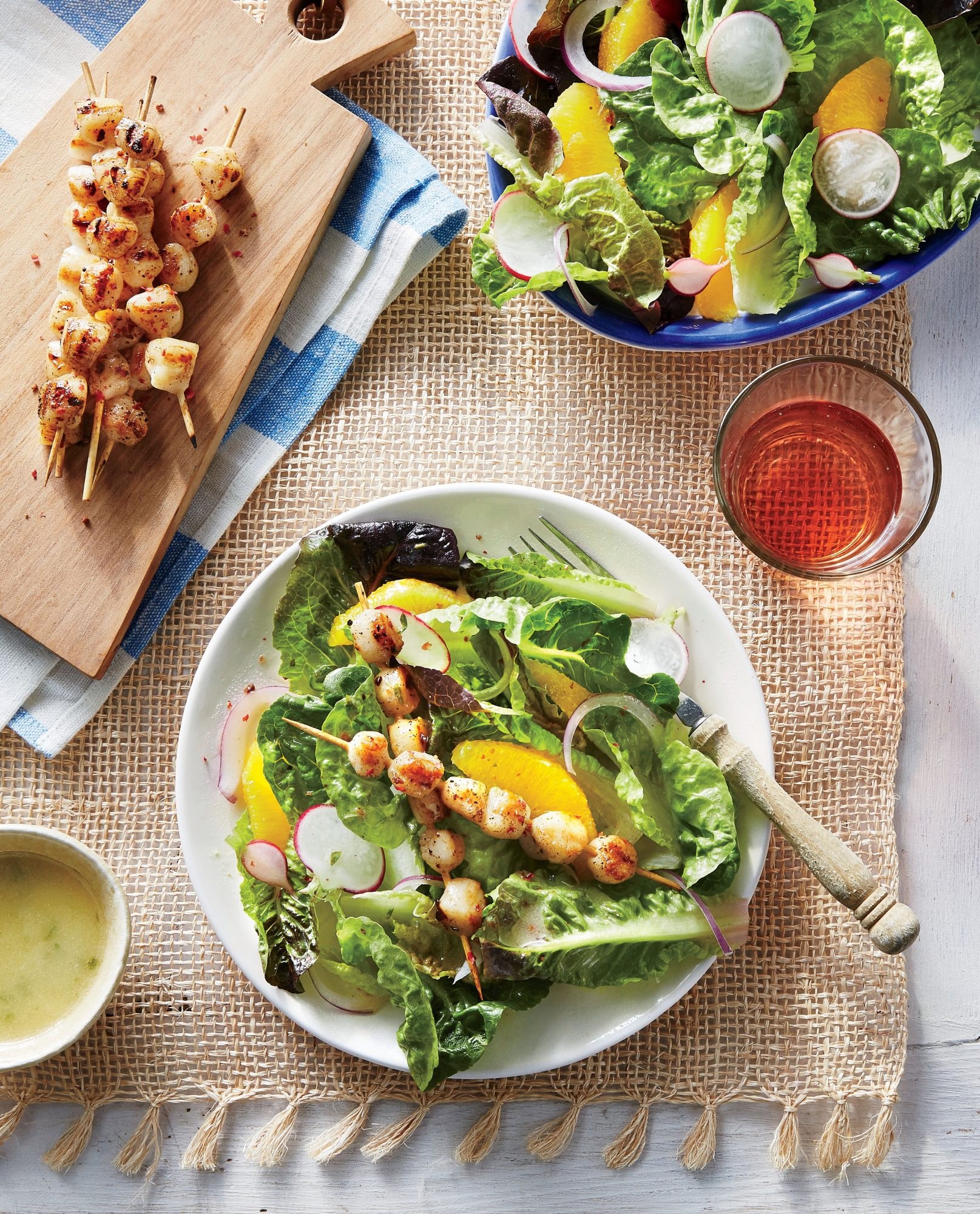 The tang of the citrus vinaigrette is the secret weapon tossed into this mixture of crispy leafy greens, grilled bay scallops, and orange slices.