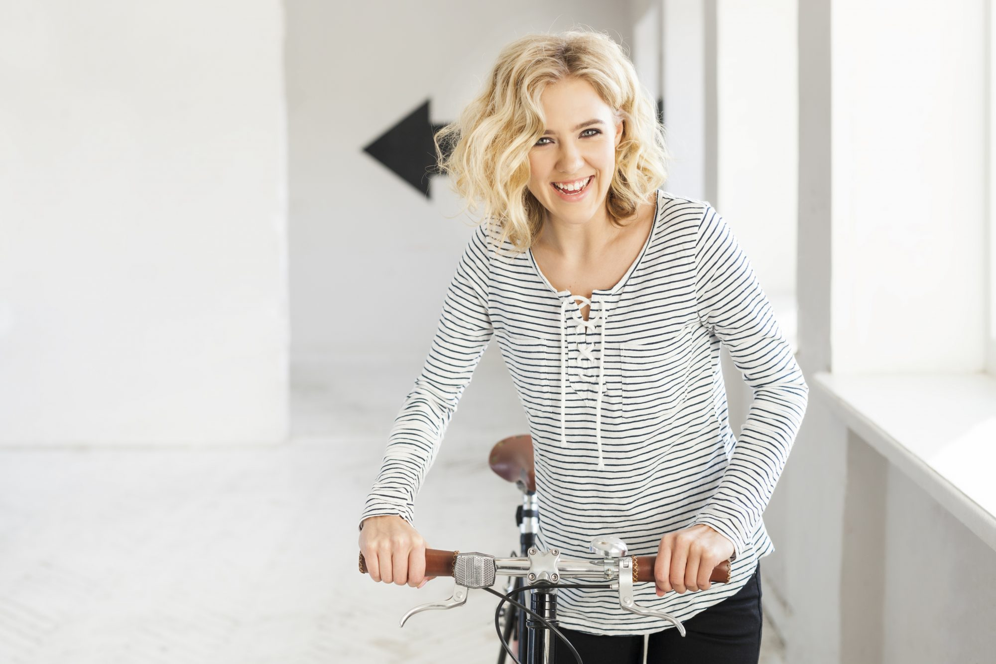 Woman with Blond Curly Hair on Bike Smiling