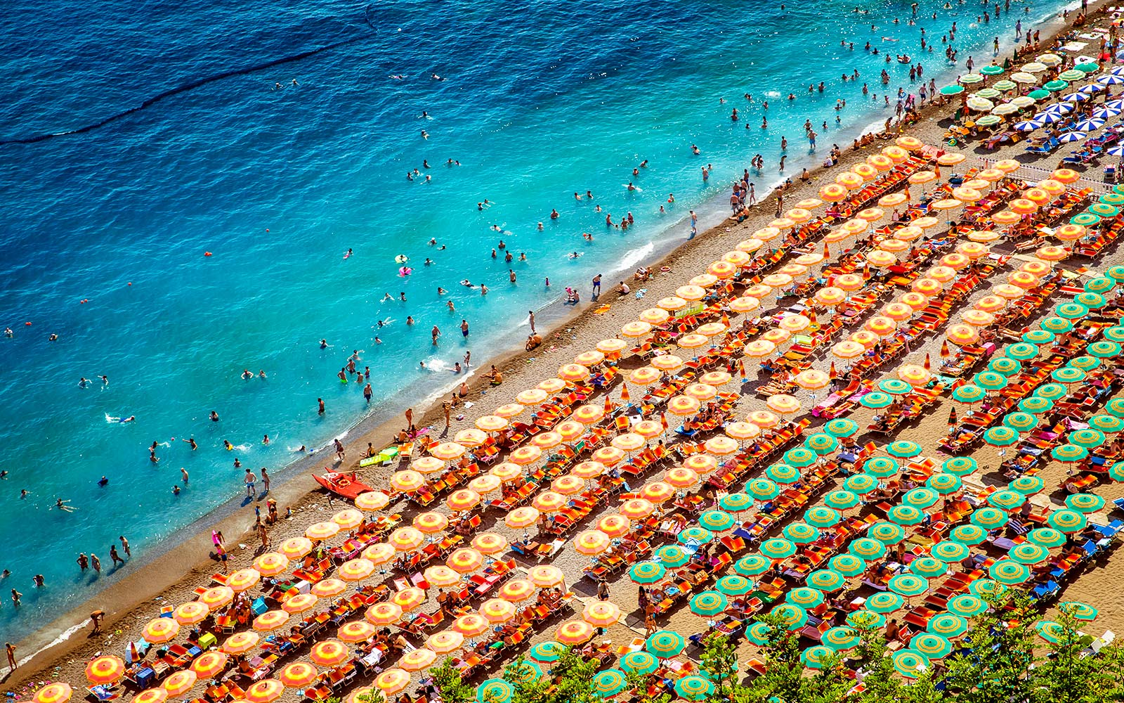 Tourists sunbath in Positano, Italy beach summer aerial
