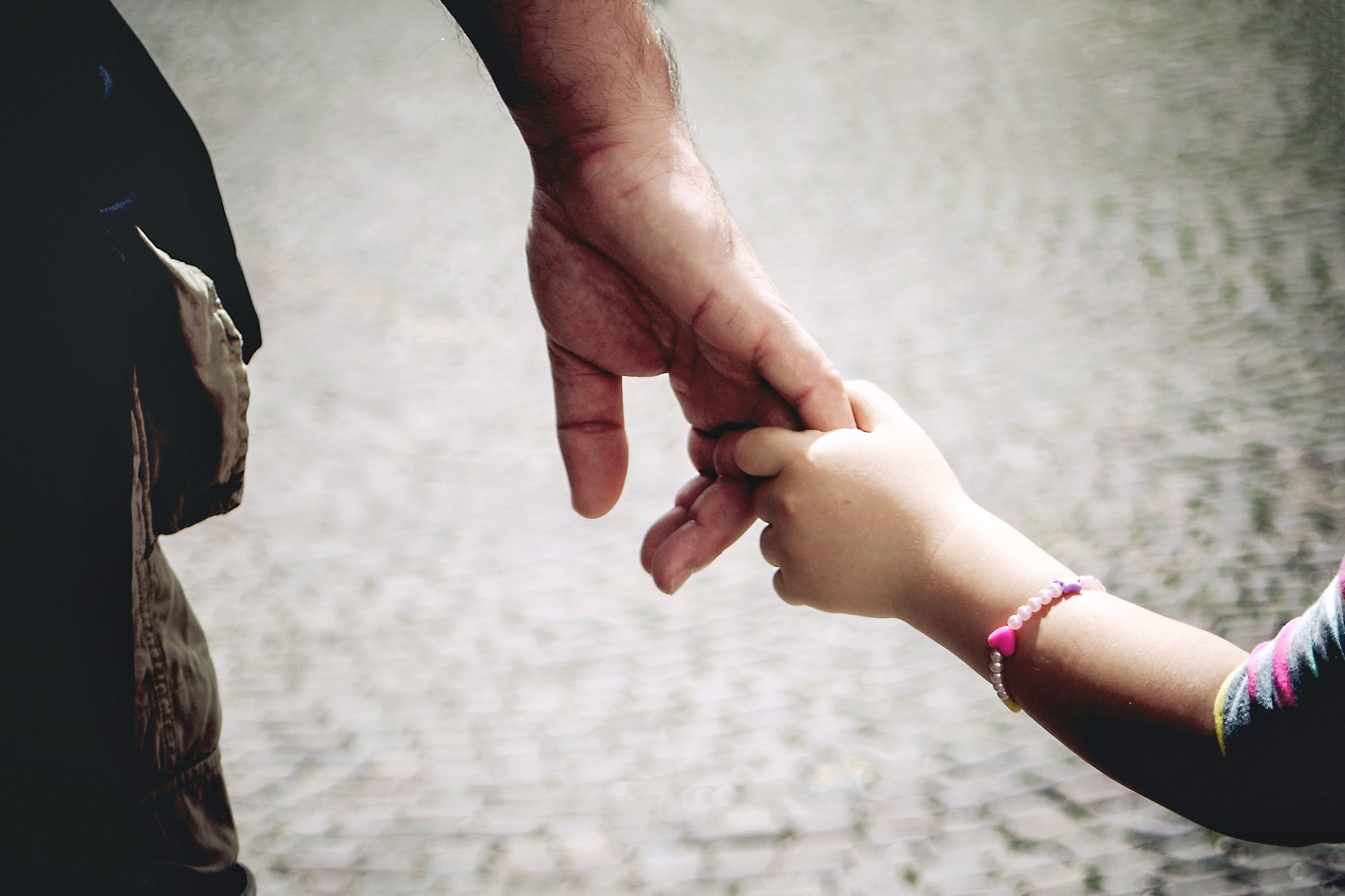 Dad holds onto little girls hand