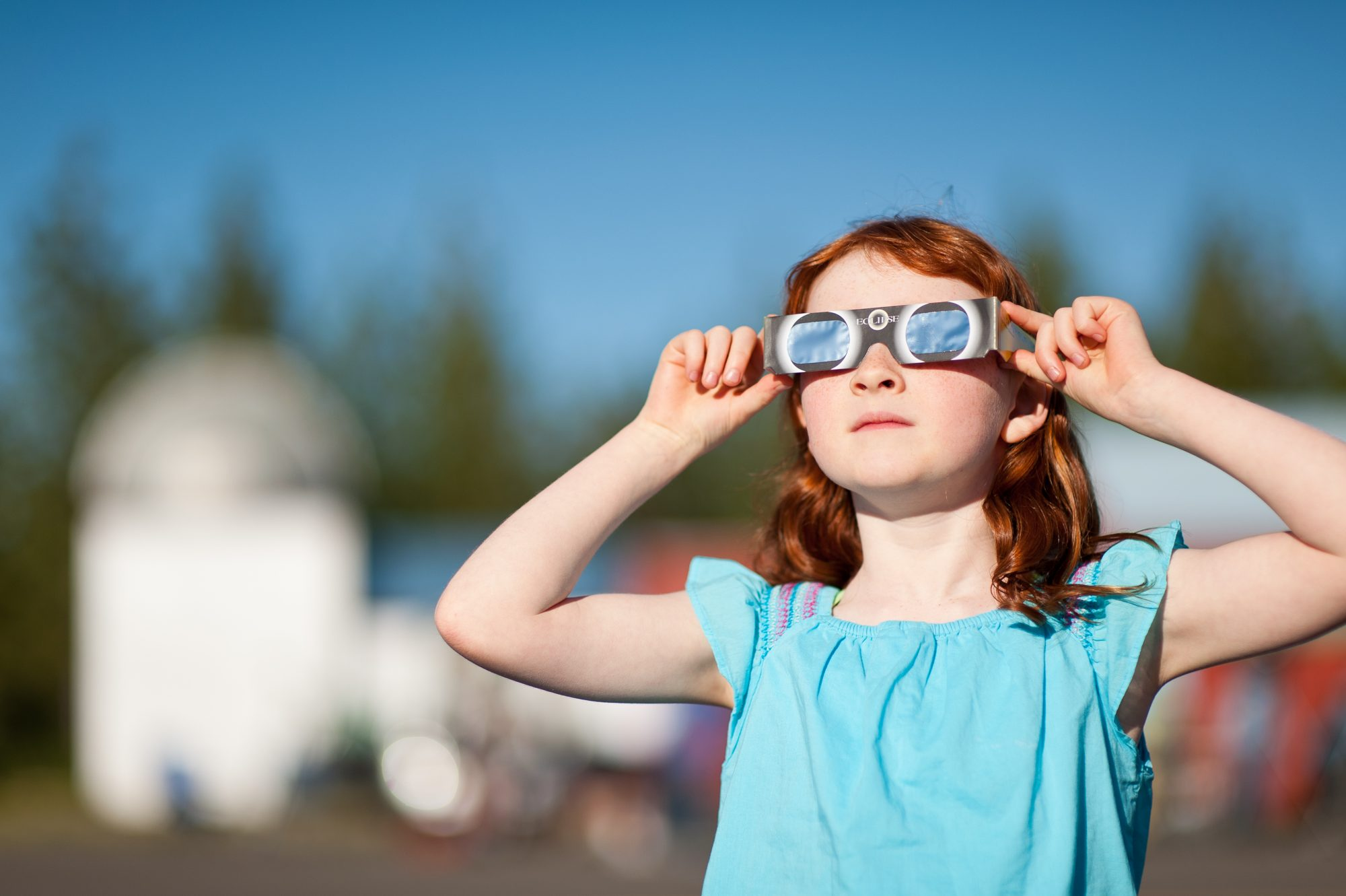 girl wearing solar eclipse glasses