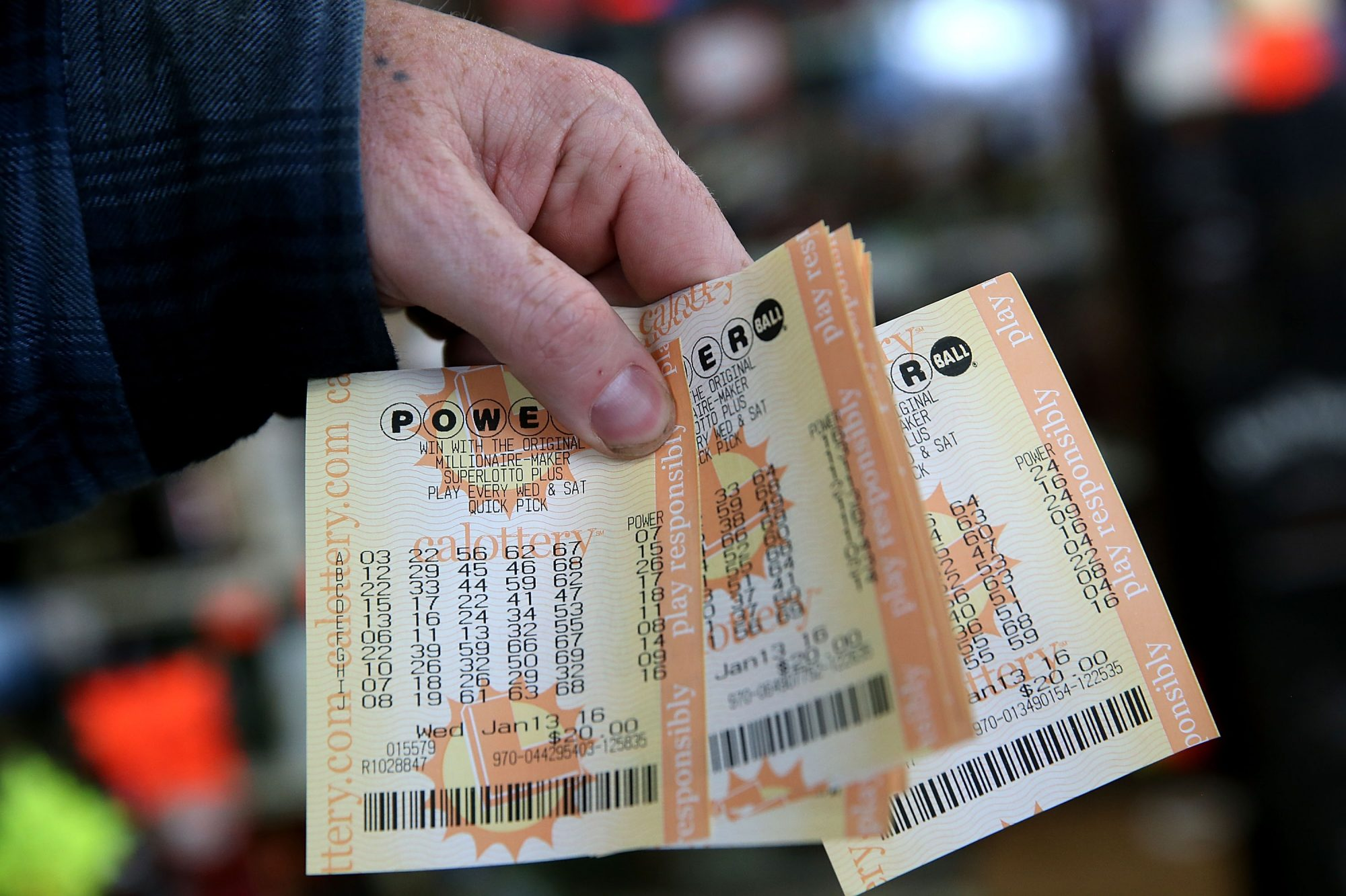 hand holding several Powerball lottery tickets
