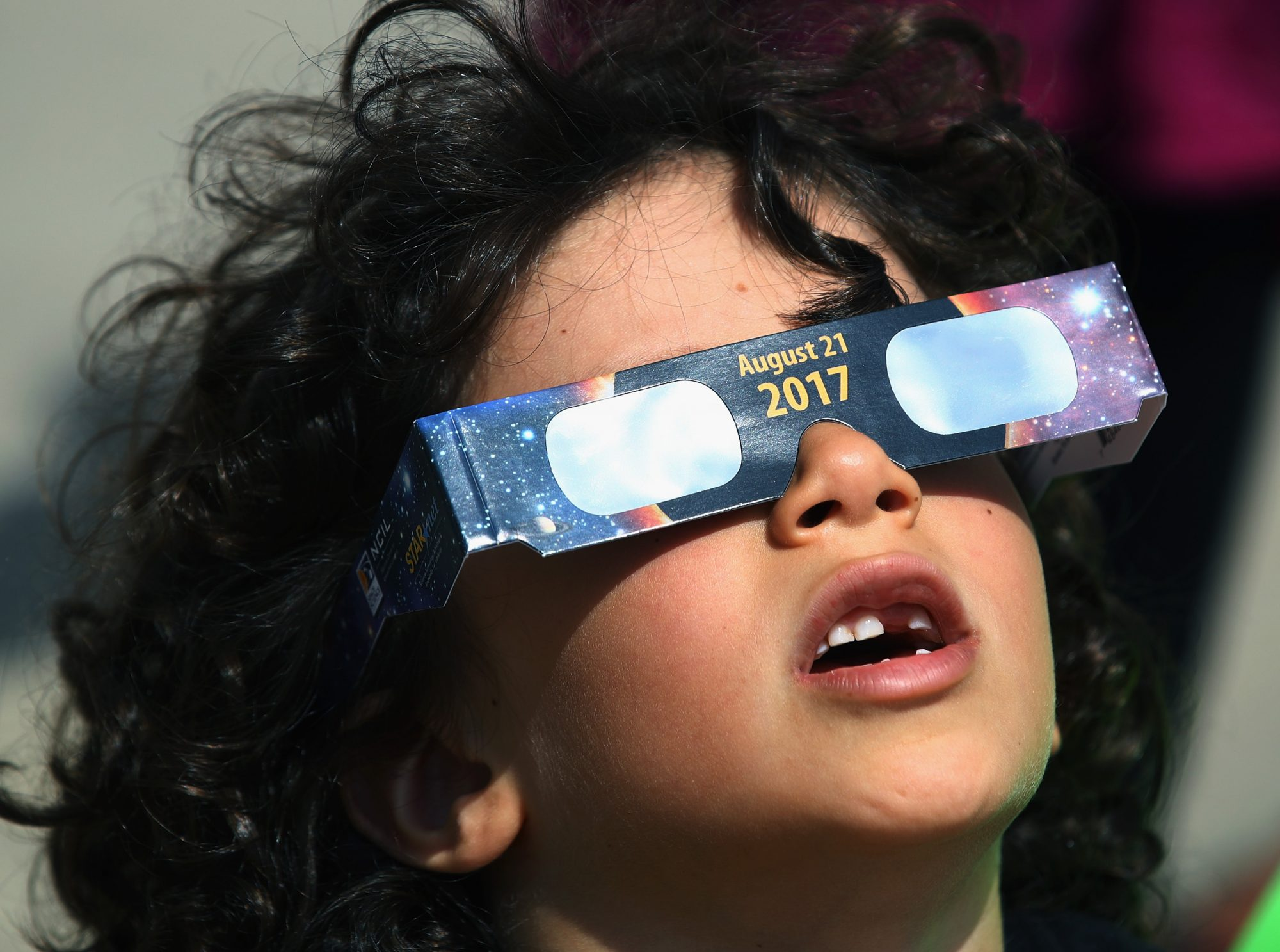 little boy in eclipse glasses