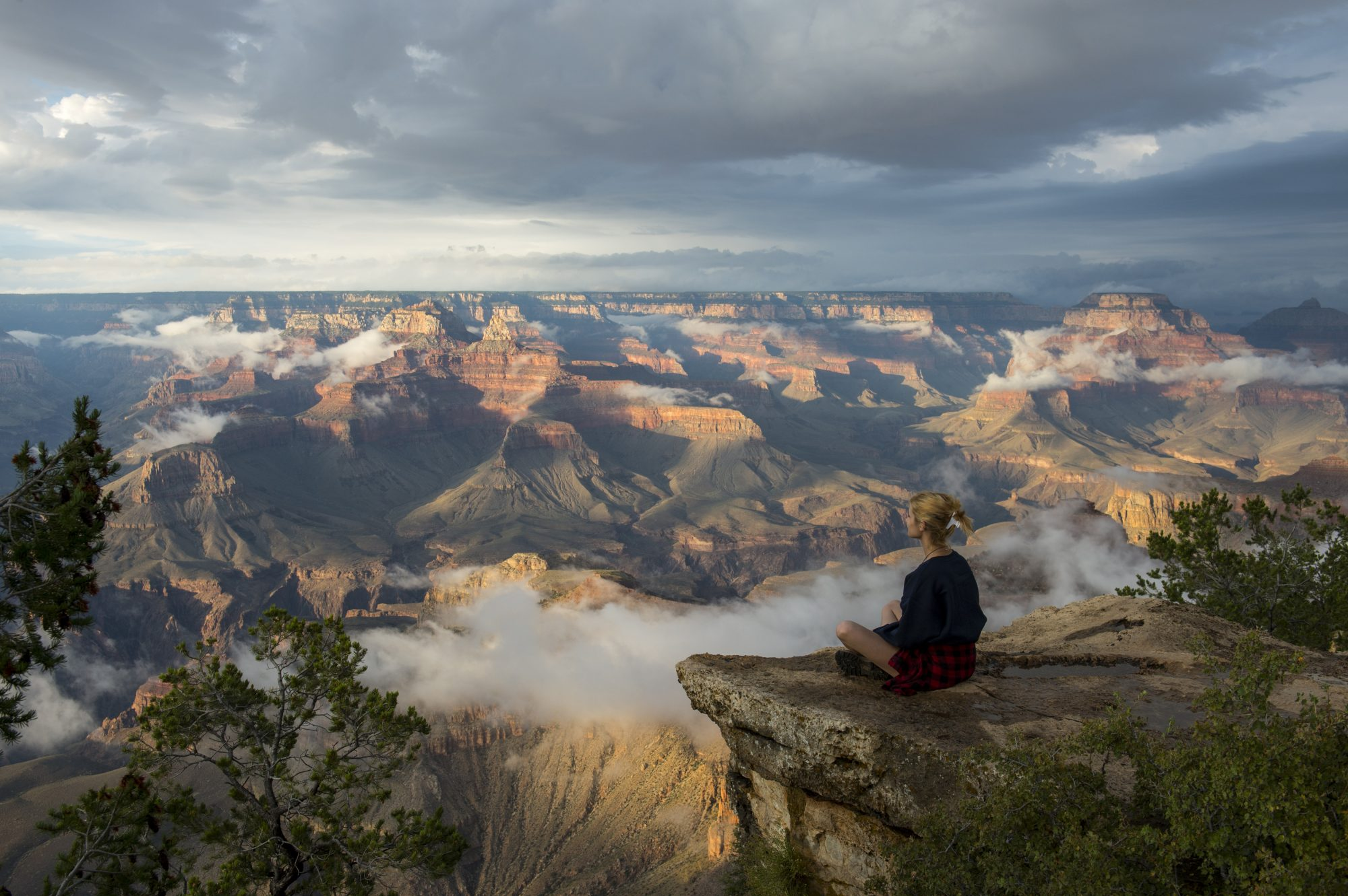 Woman Sitting on a Cliff Overlooking the Grand Canyon