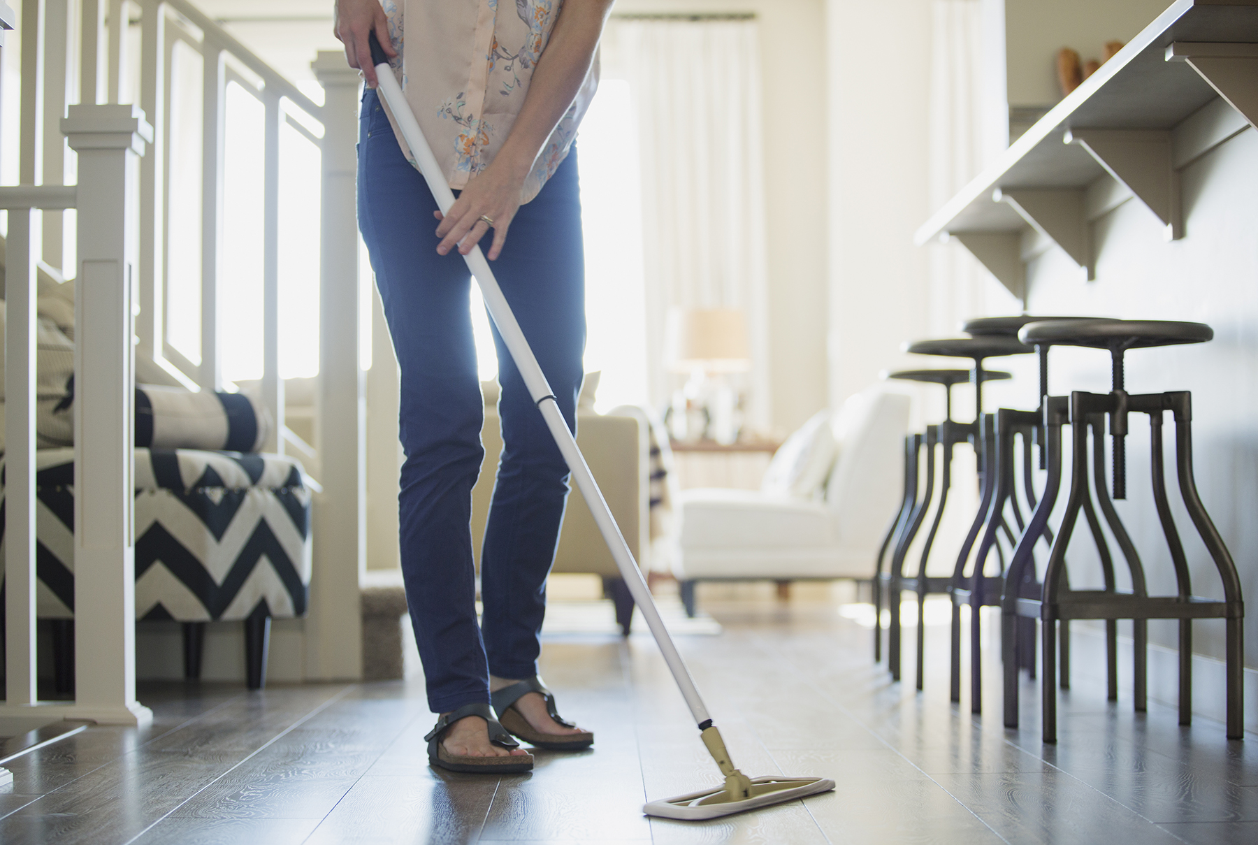 Woman dust-mopping floor