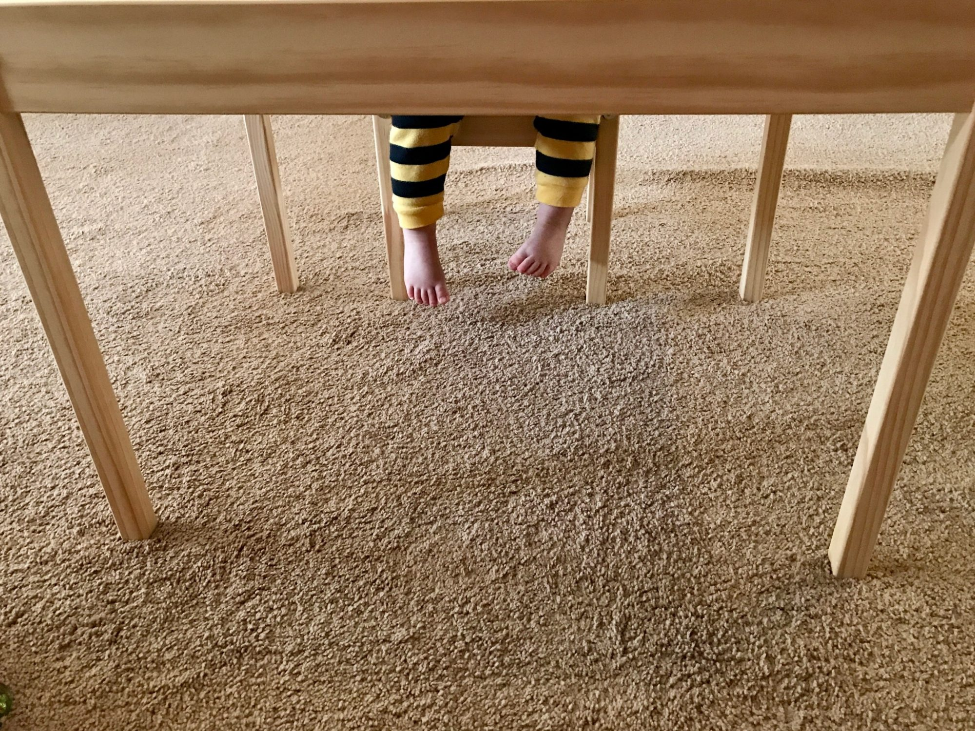 Little boy's feet dangling over carpet