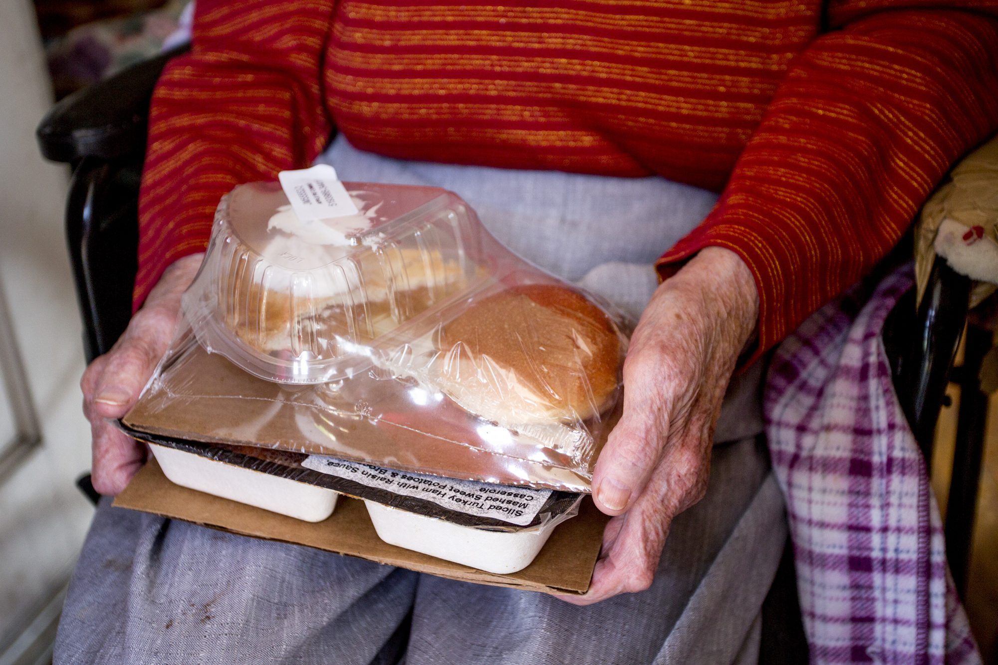 Close Up Elderly Hands Holding Packaged Meal