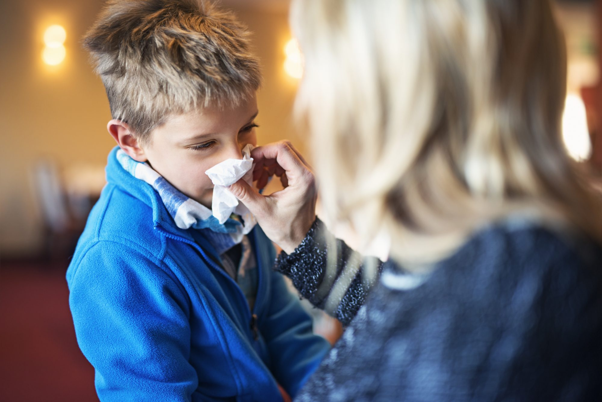Boy Blowing His Nose with Help from Mom