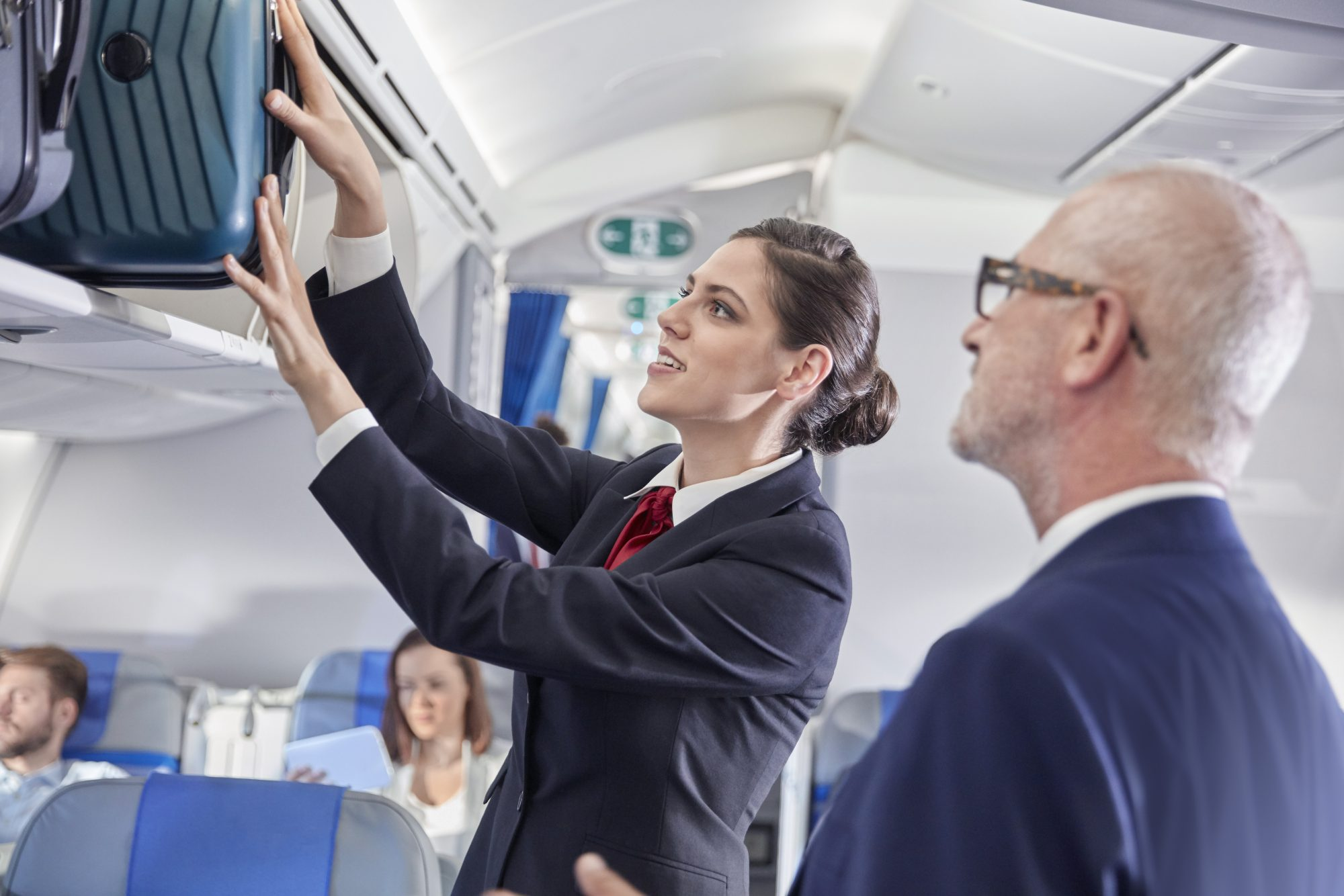 Flight Attendant Helping Man with Overhead Bin