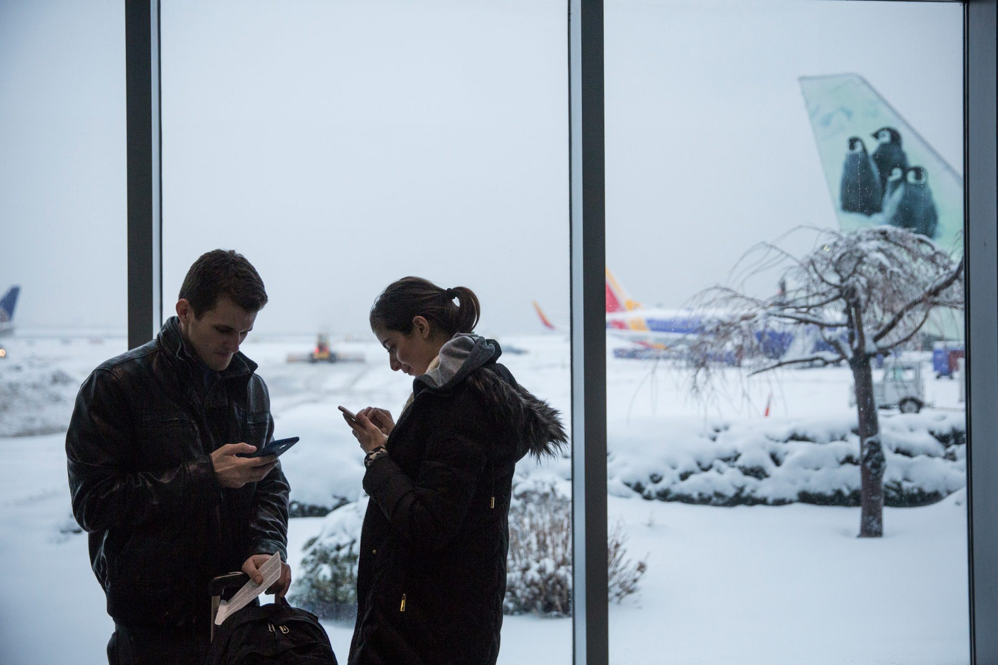 Man and Woman at Snowy Airport Gate
