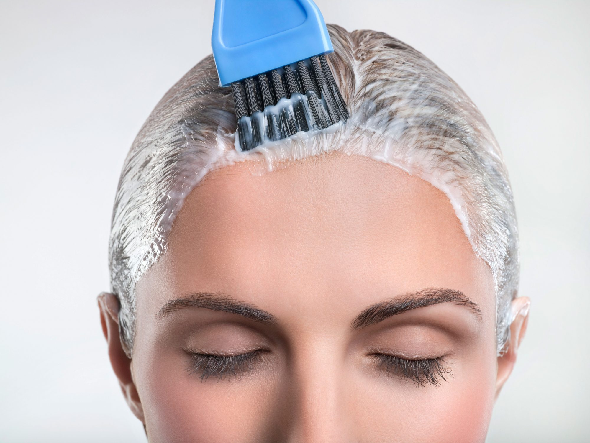 Woman Applying Hair Color All Over Head