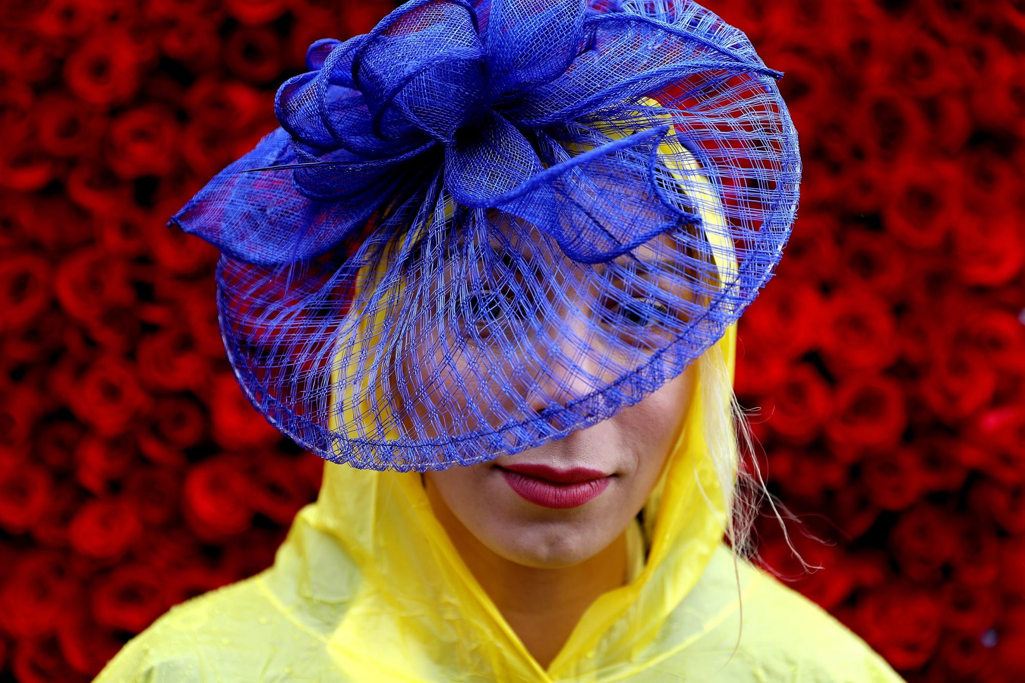 A woman wearing a festive hat poses prior to the 143rd running of the Kentucky Derby