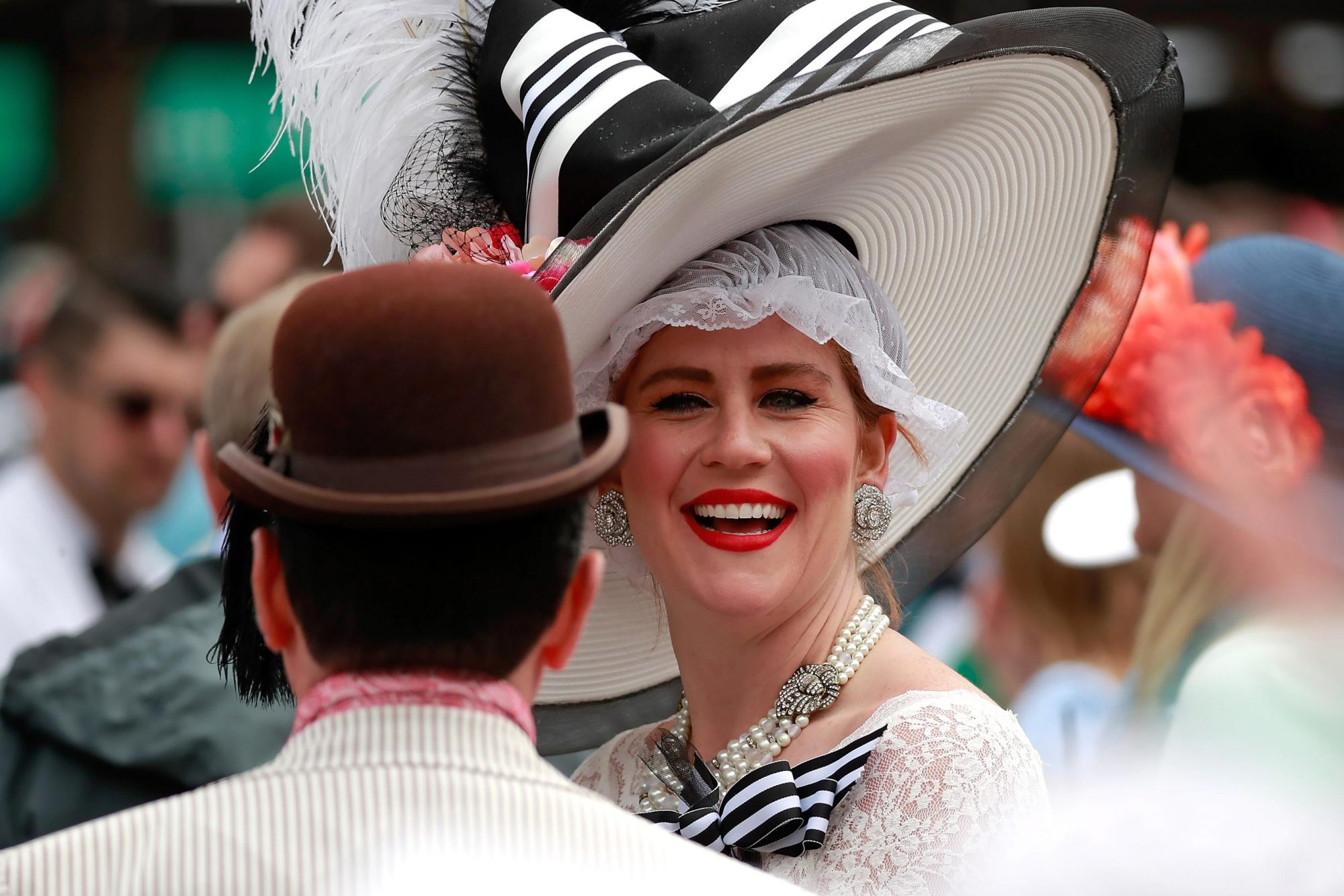 A woman wearing a festive hat looks on prior to the 143rd running of the Kentucky Derby