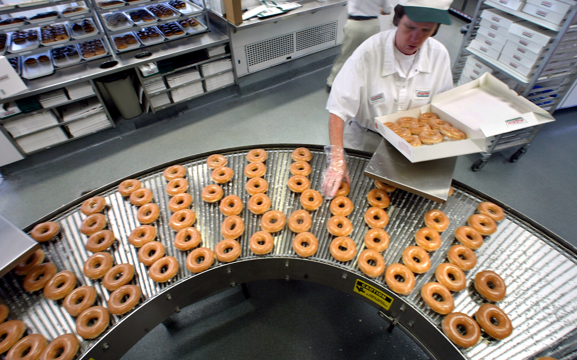 This is a profile of the Krispy Kreme chain. Here, Gloria Yates boxes a dozen original glazed doughn
