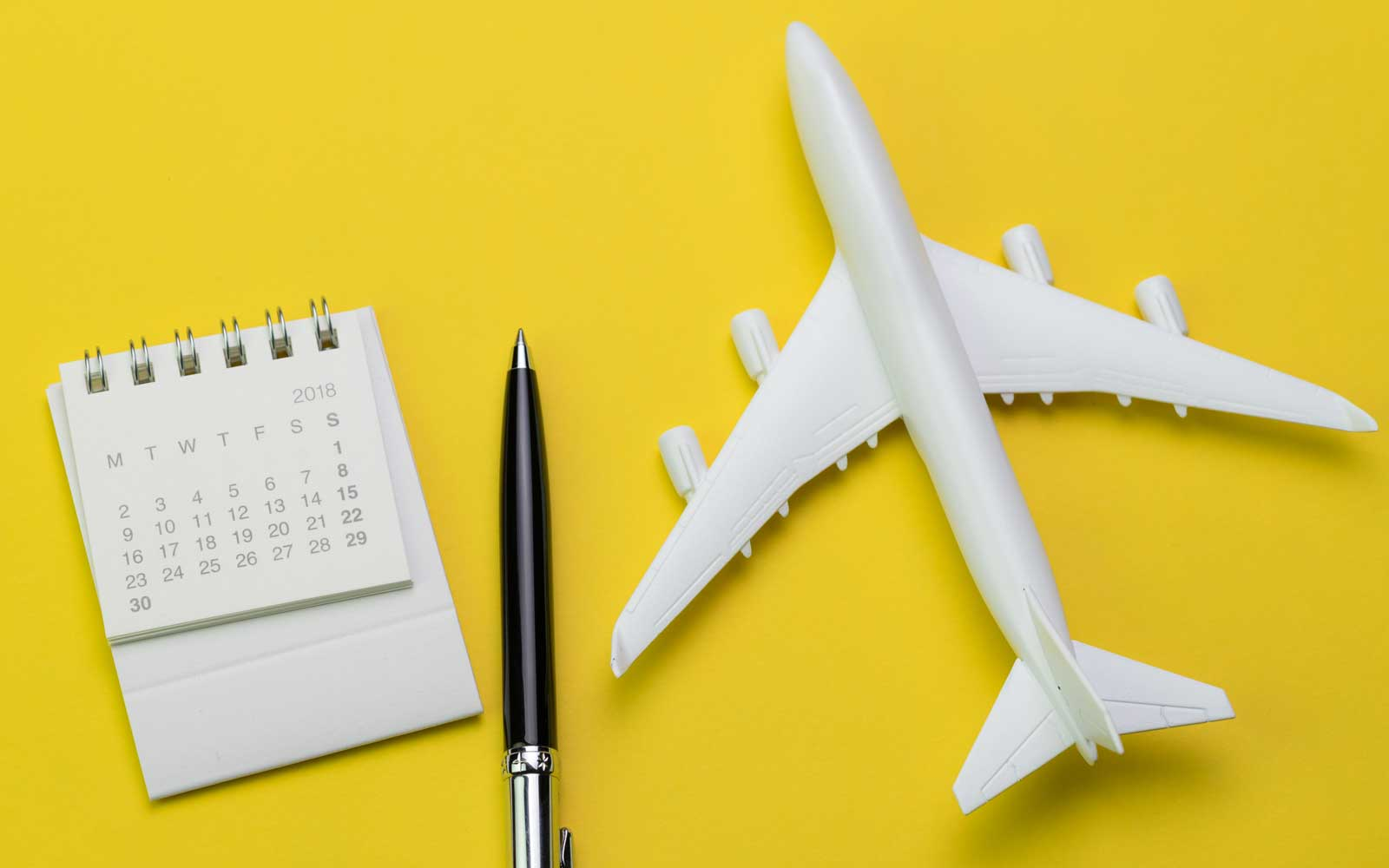 Still life of 2018 calendar, pen, and toy plane on sunny yellow background