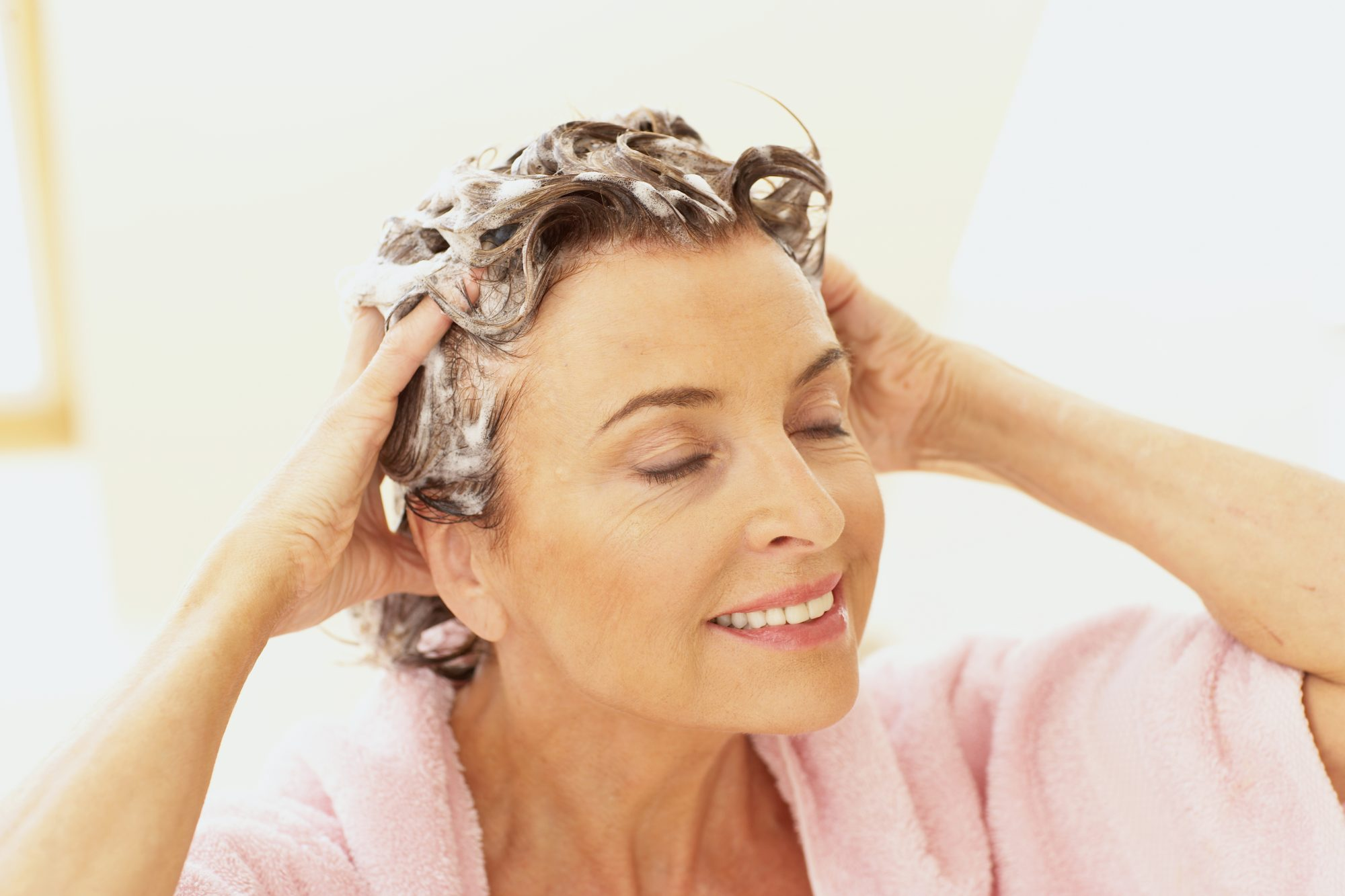 Older Woman Washing Hair in Pink Robe