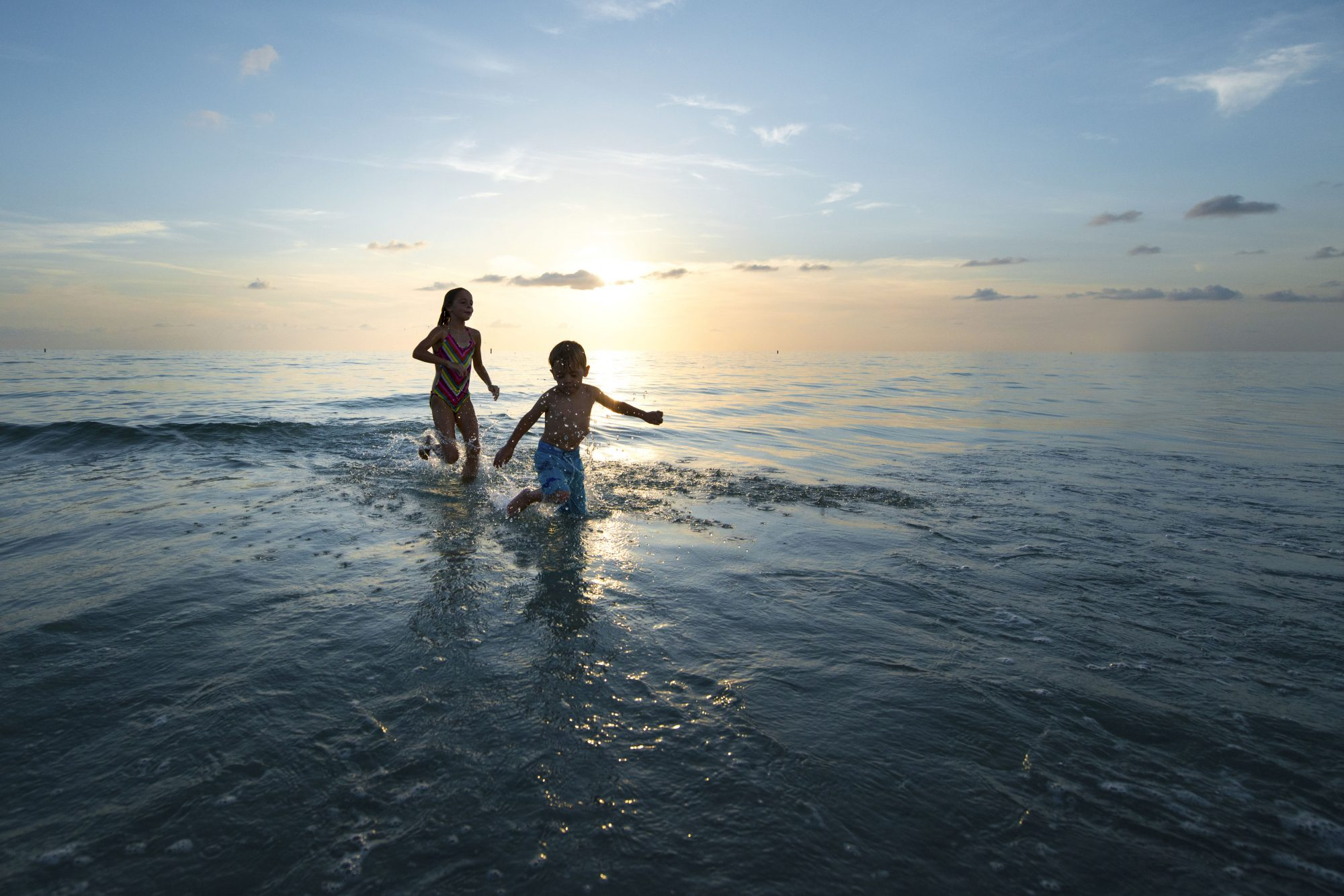 Young girl and boy running in ocean at sunset in Florida, USA.