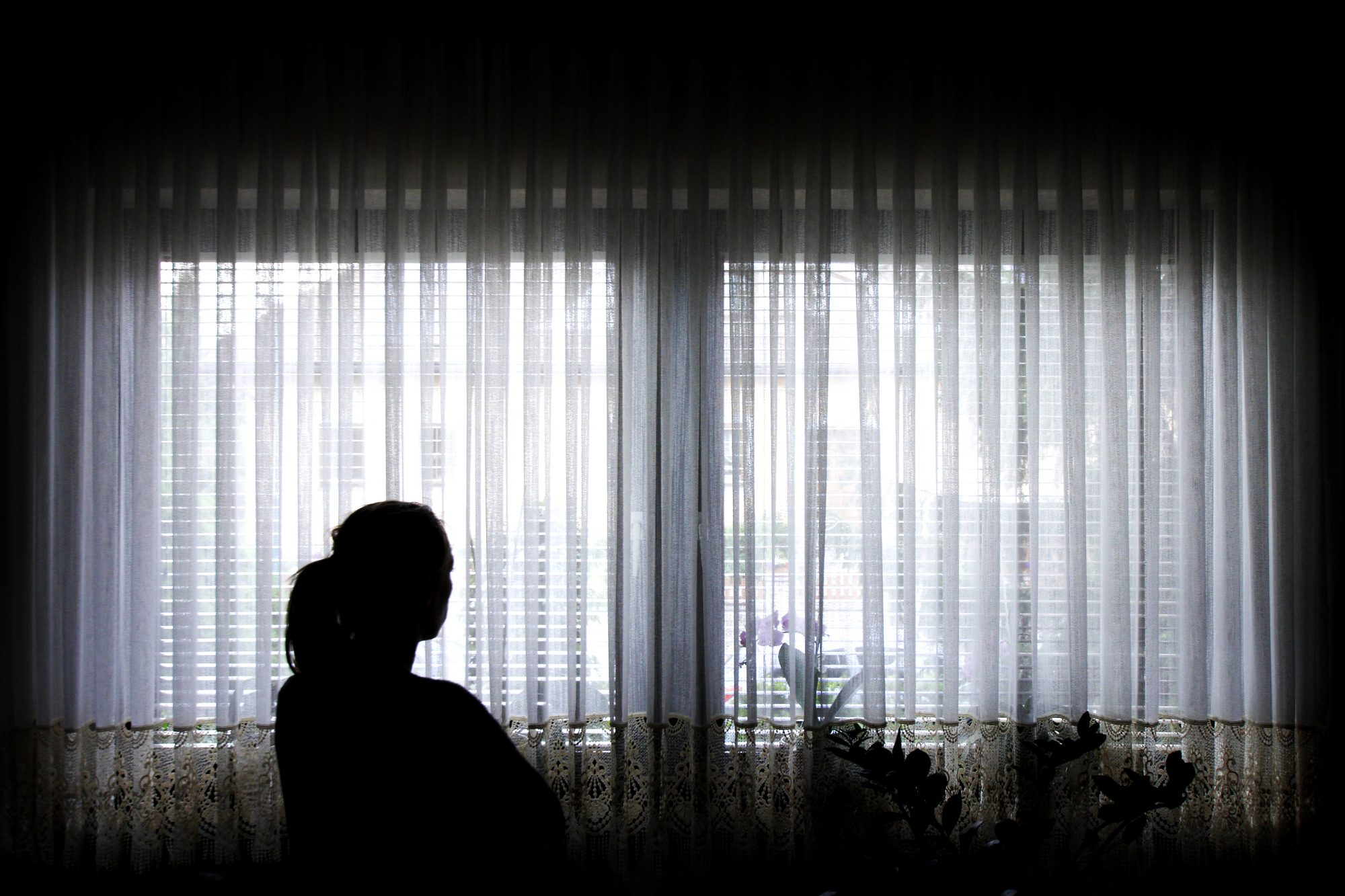 Silhouette of Woman Staring Out Window
