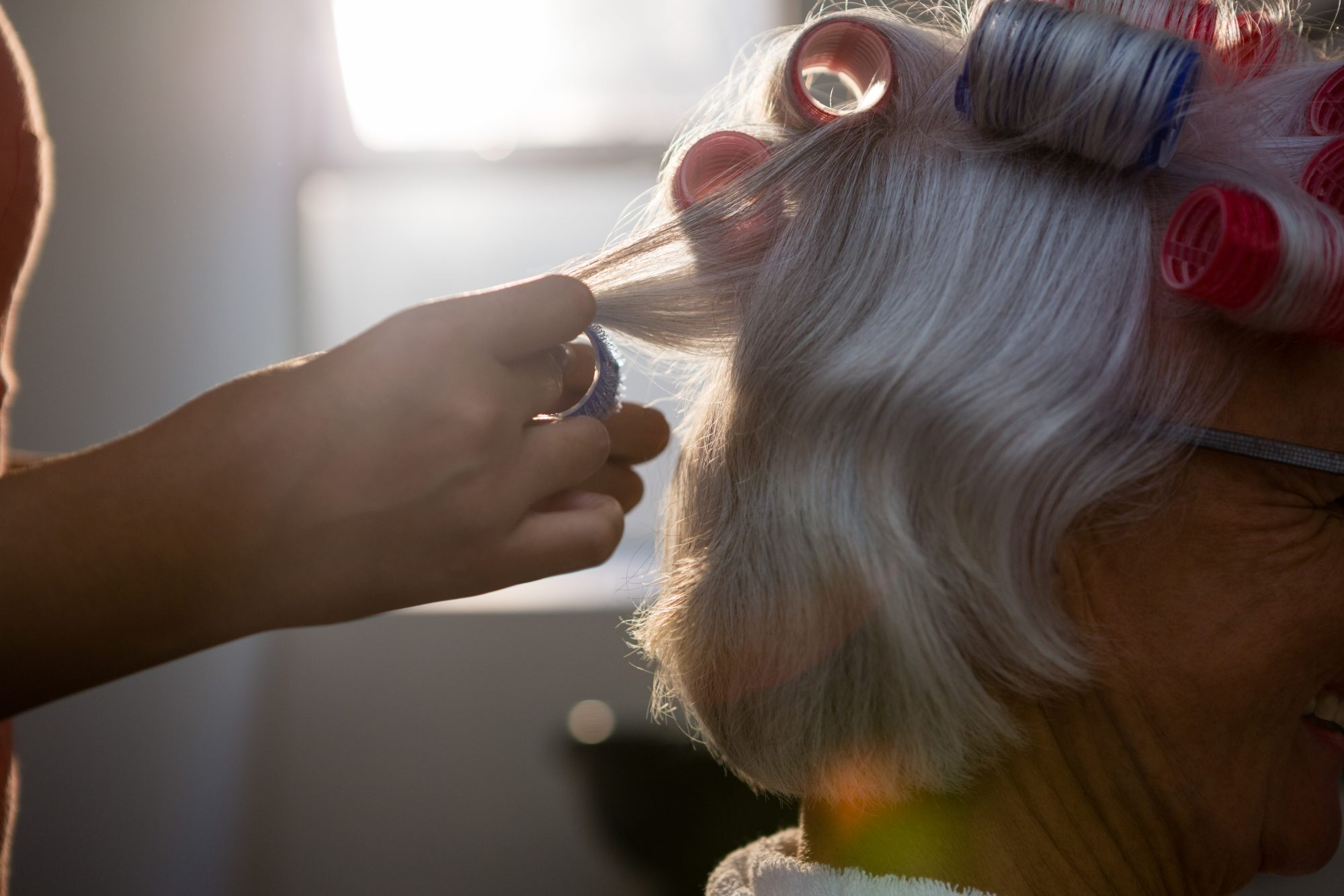 Woman Getting Curlers In Gray Hair