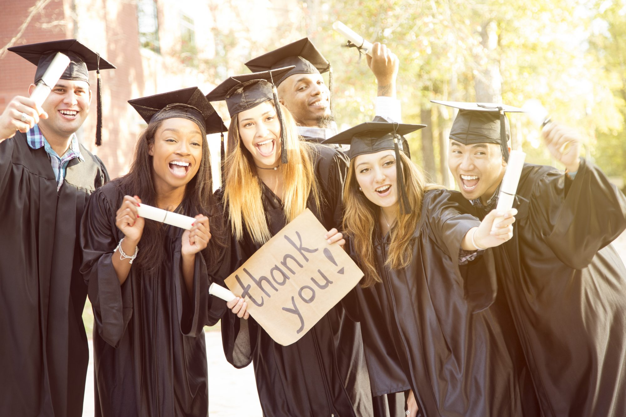 Graduates Holding Thank You Sign