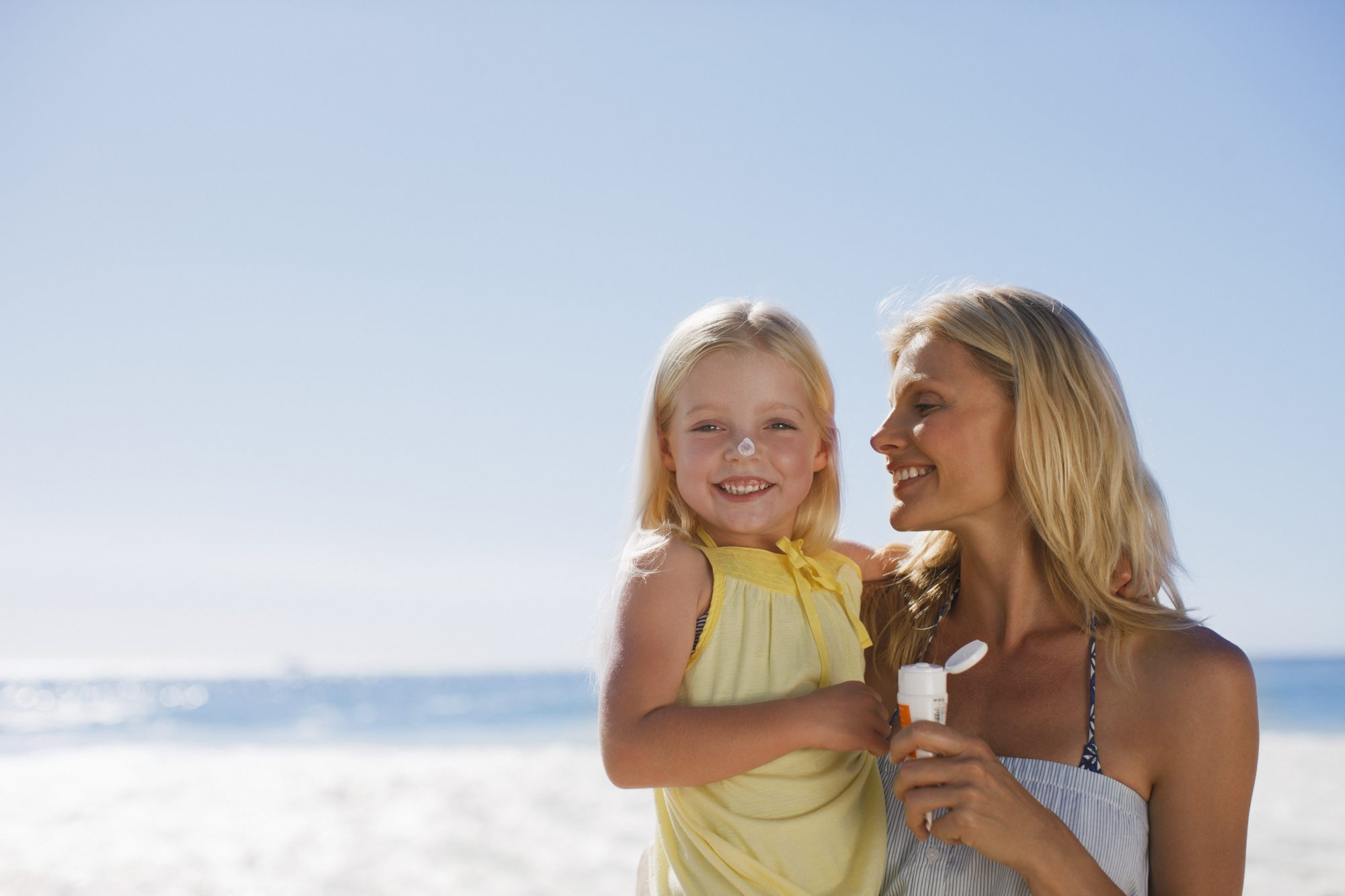 Mother and Daughter Applying Sunscreen at the Beach