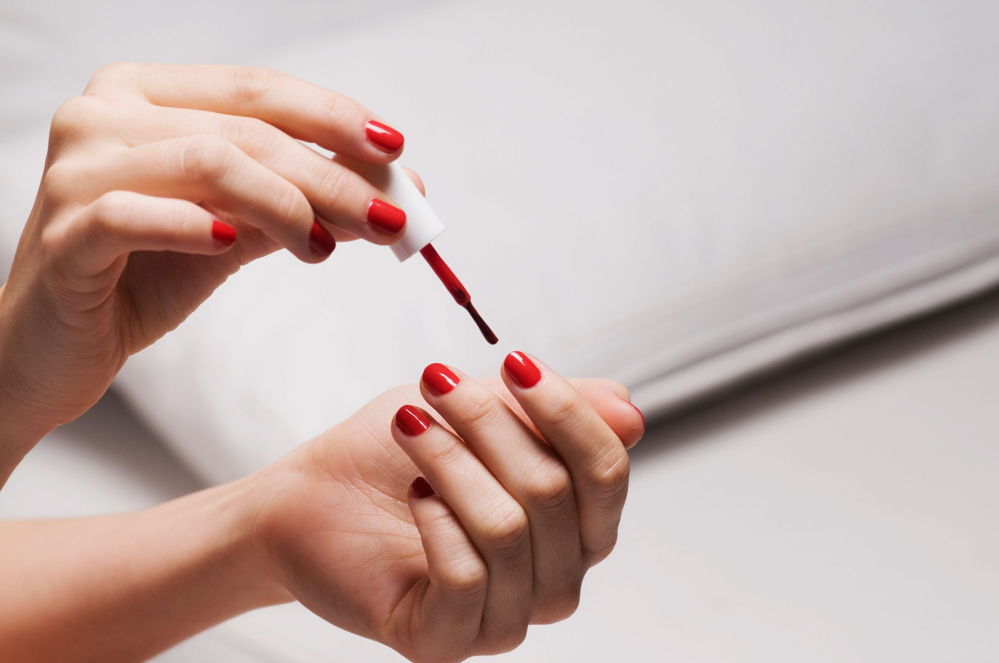 Woman Painting Nails Red