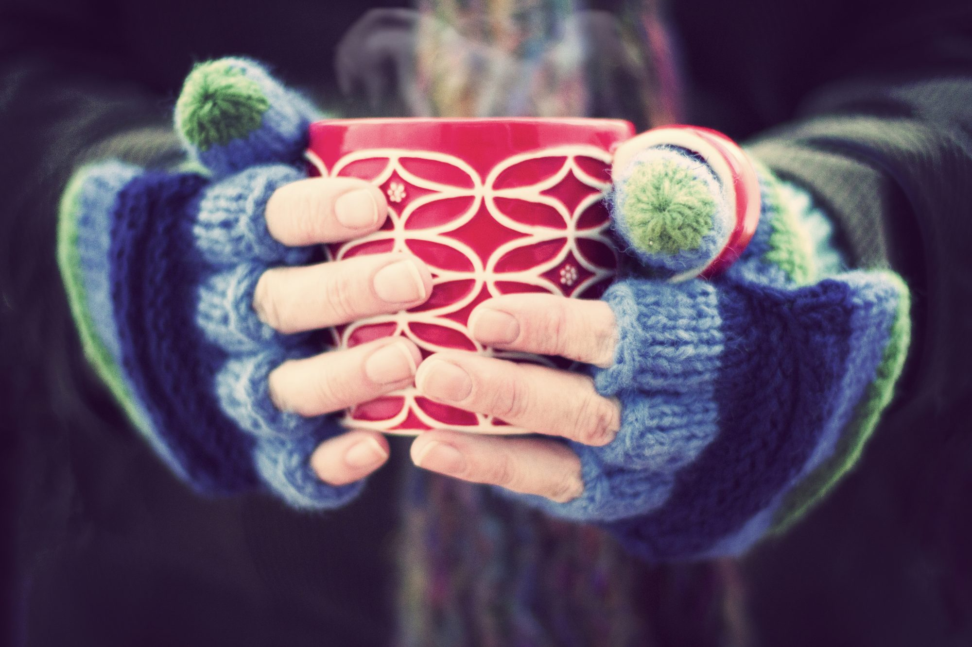 Gloved Hands Grasping Warm Mug