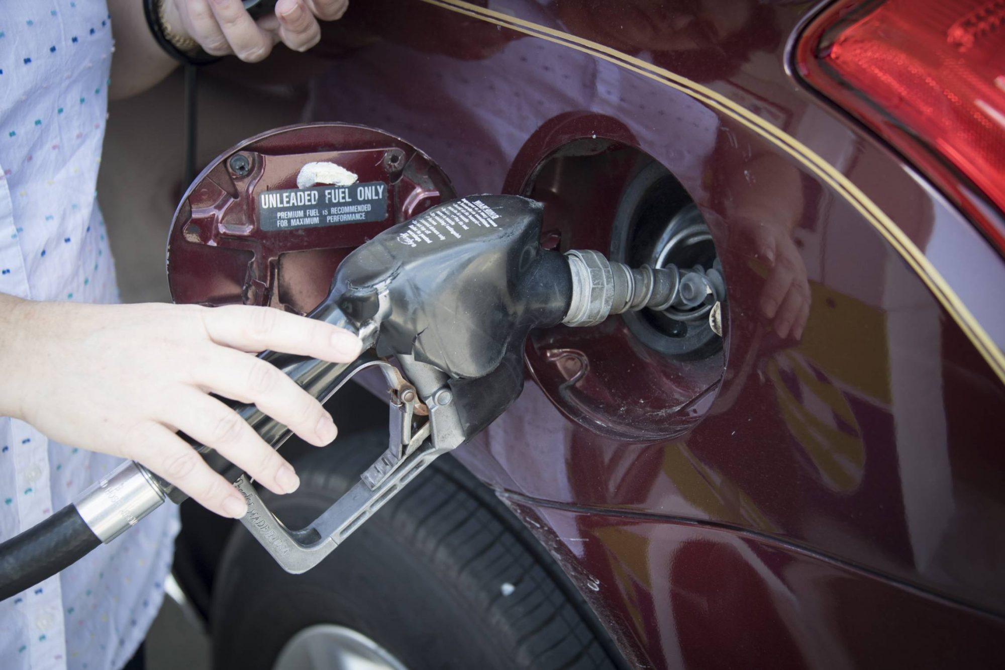 Woman's hand holding a pump nozzle in car fuel tank door.
