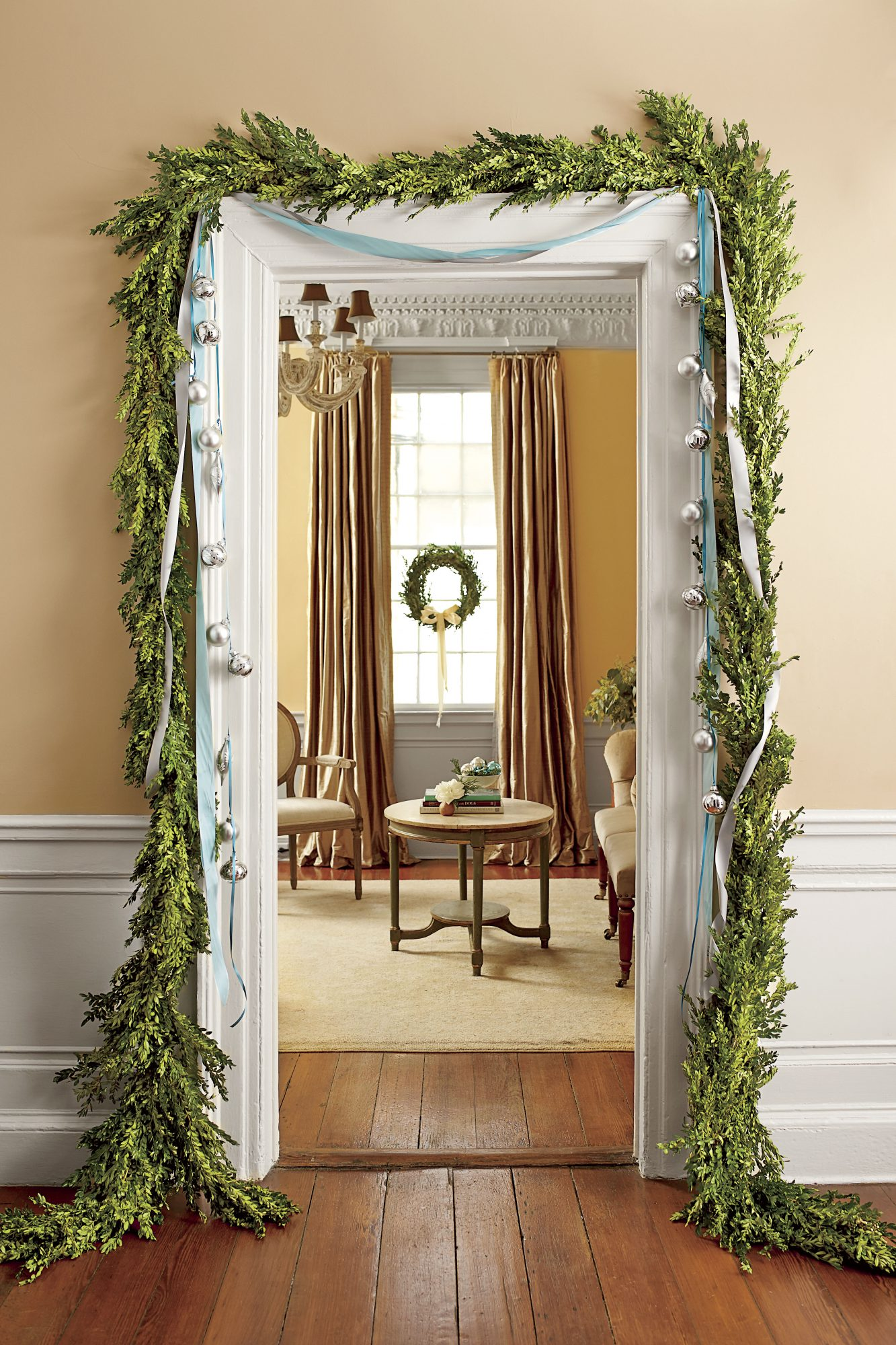 Boxwood Garland with Ribbon and Ornaments Around Door frame