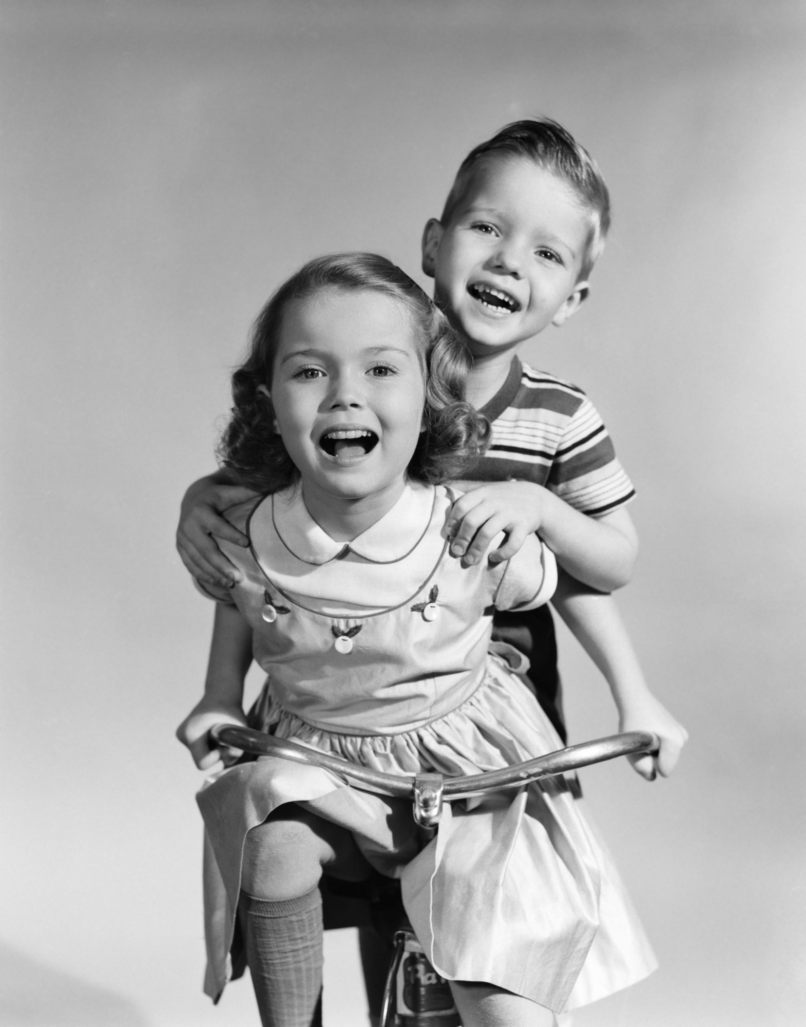 Girl Riding Bike with Boy Standing Behind Her